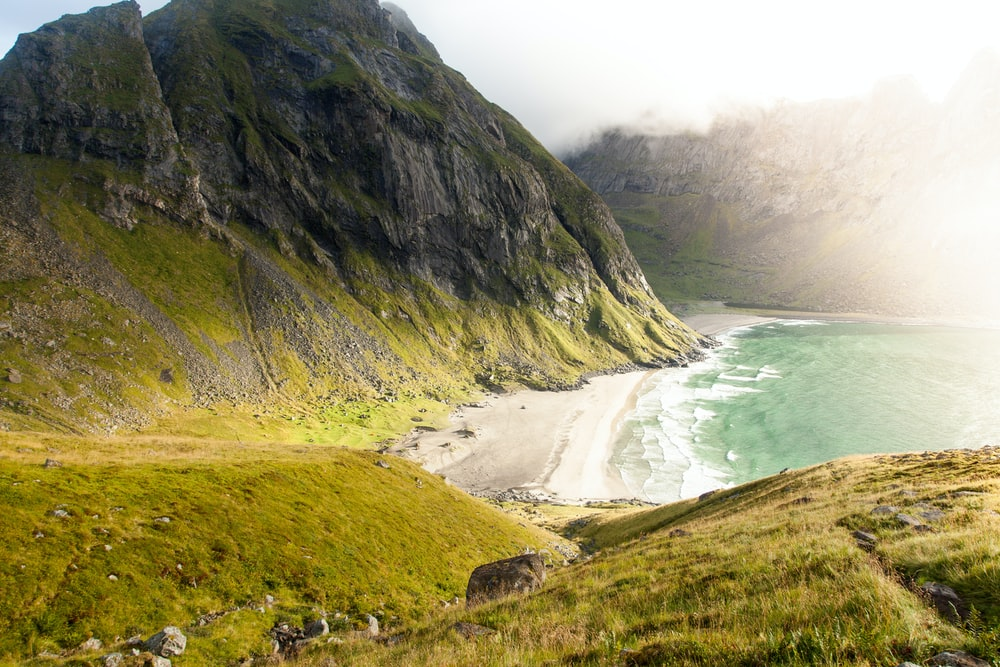 landscape photography of beach surrounded by mountains
