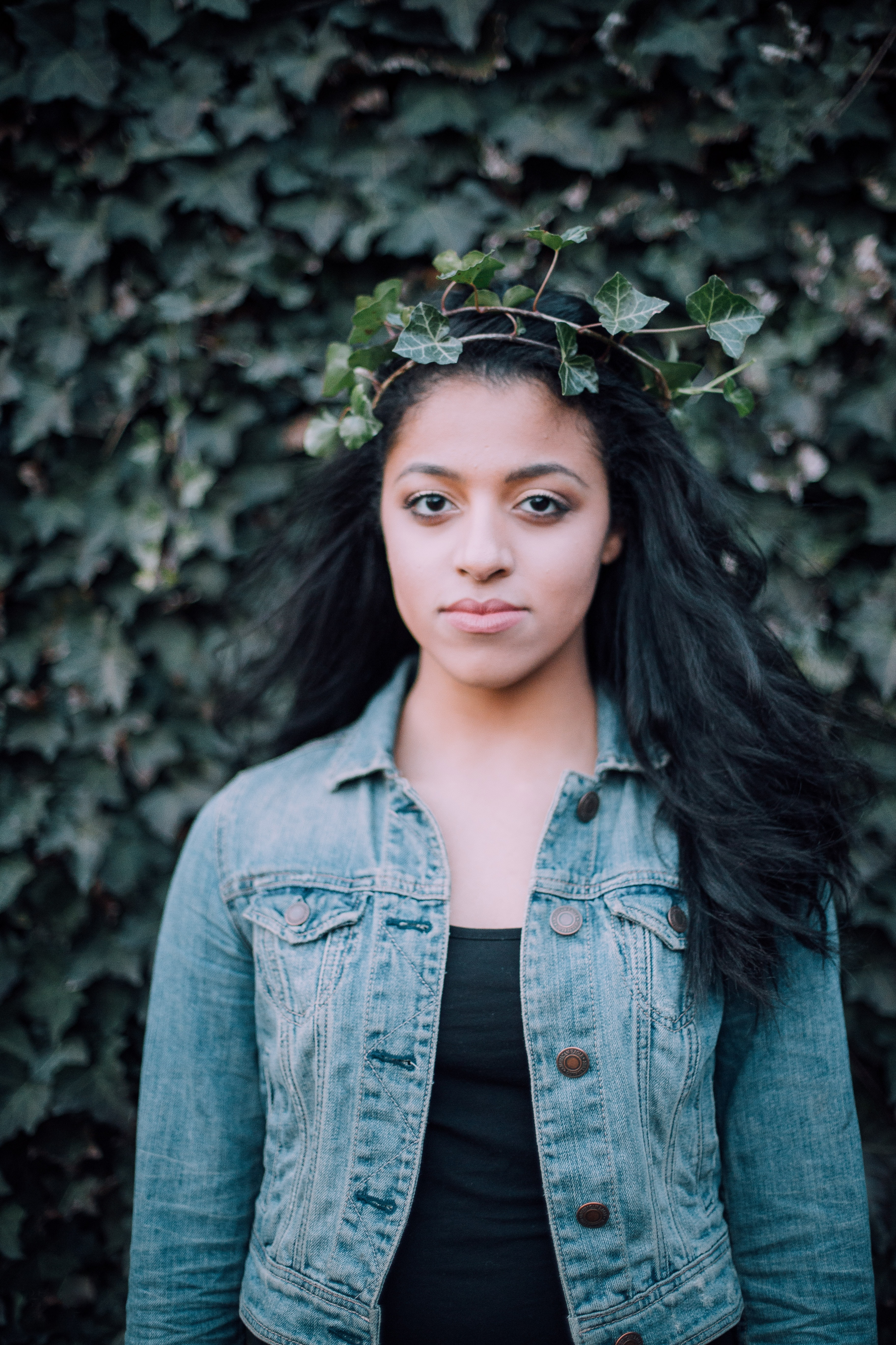 Woman wearing a crown of leaves and a denim jacket