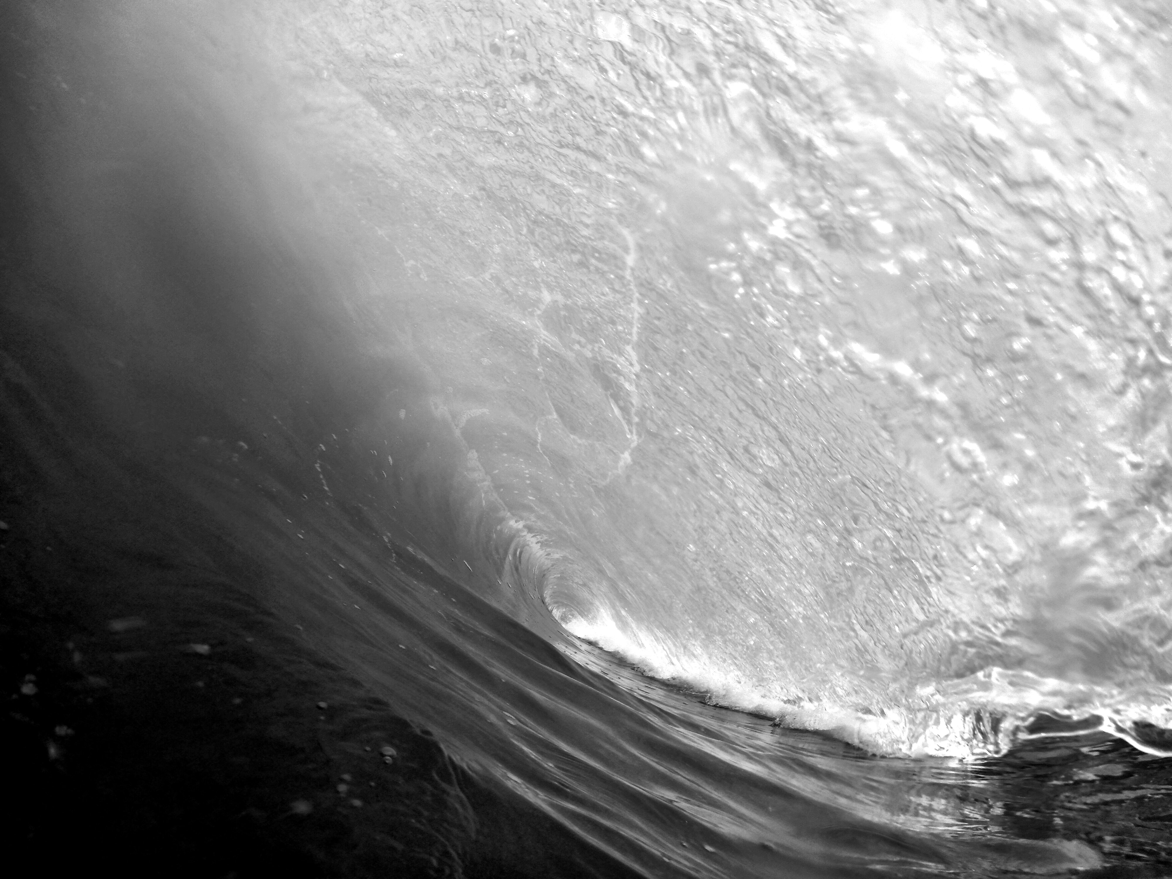 A black and white shot taken from within a rolling wave