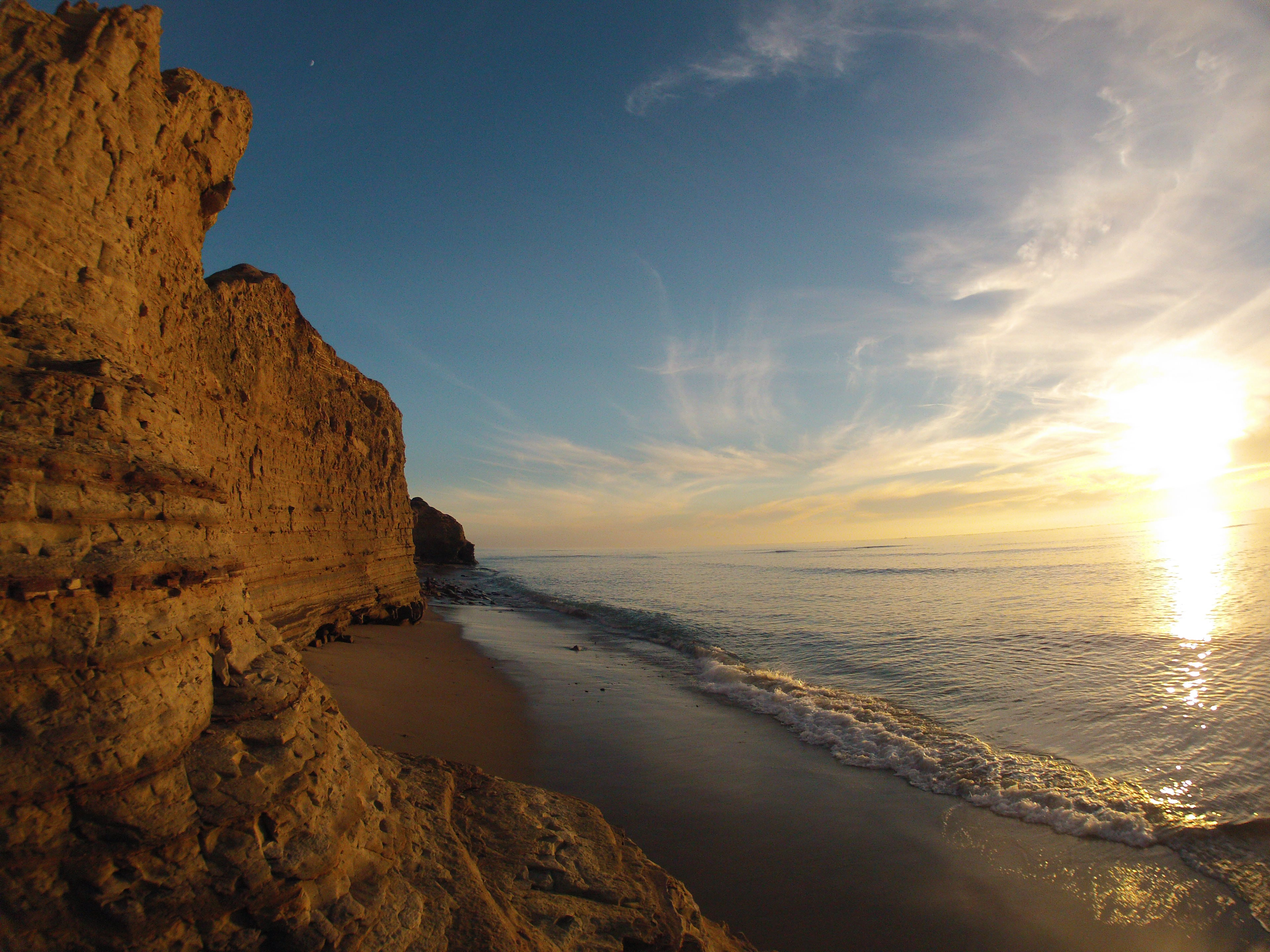 A tall rock wall behind a small beach area, taken during sunset.