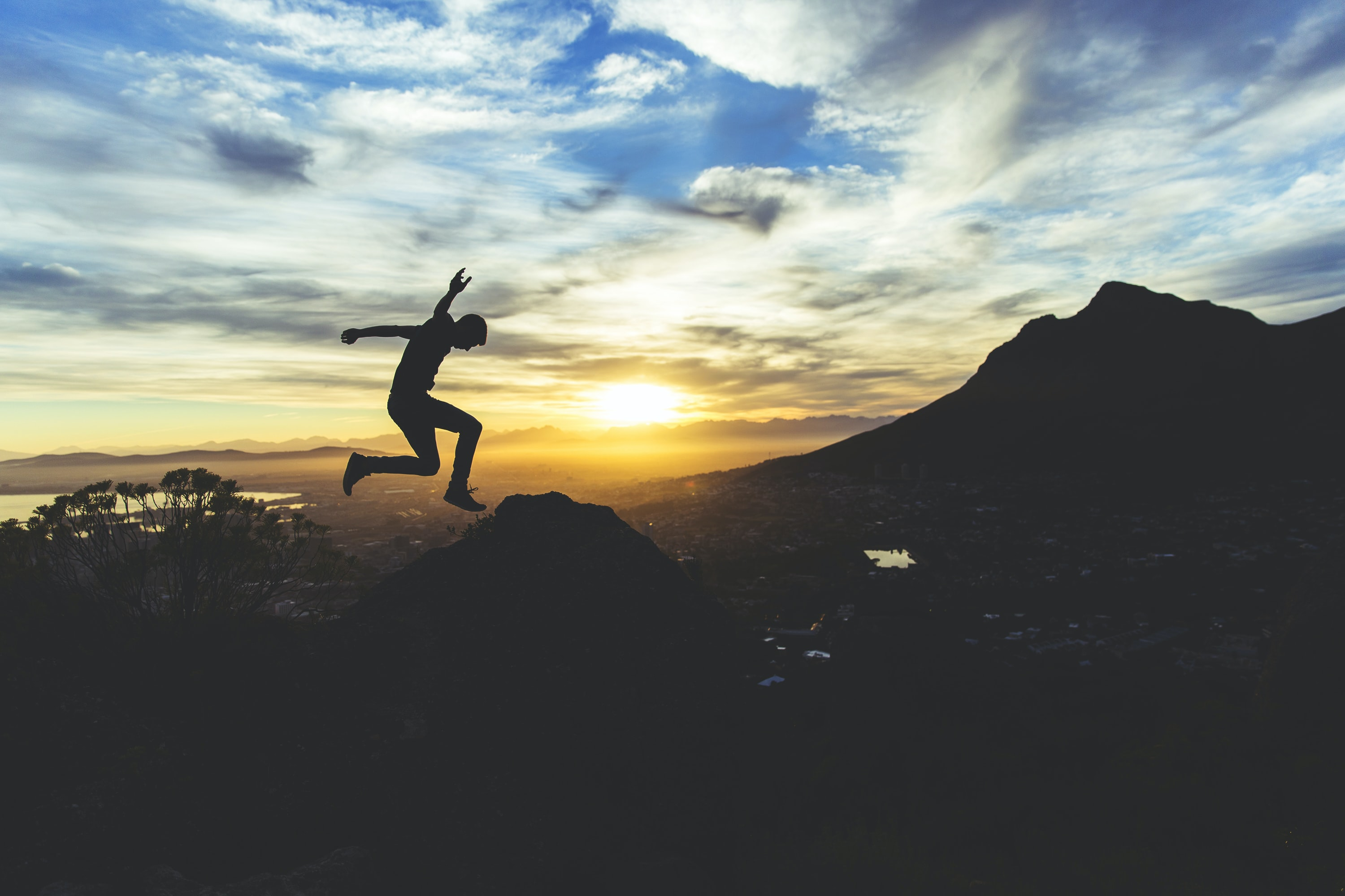 person jumping on hill during sunset