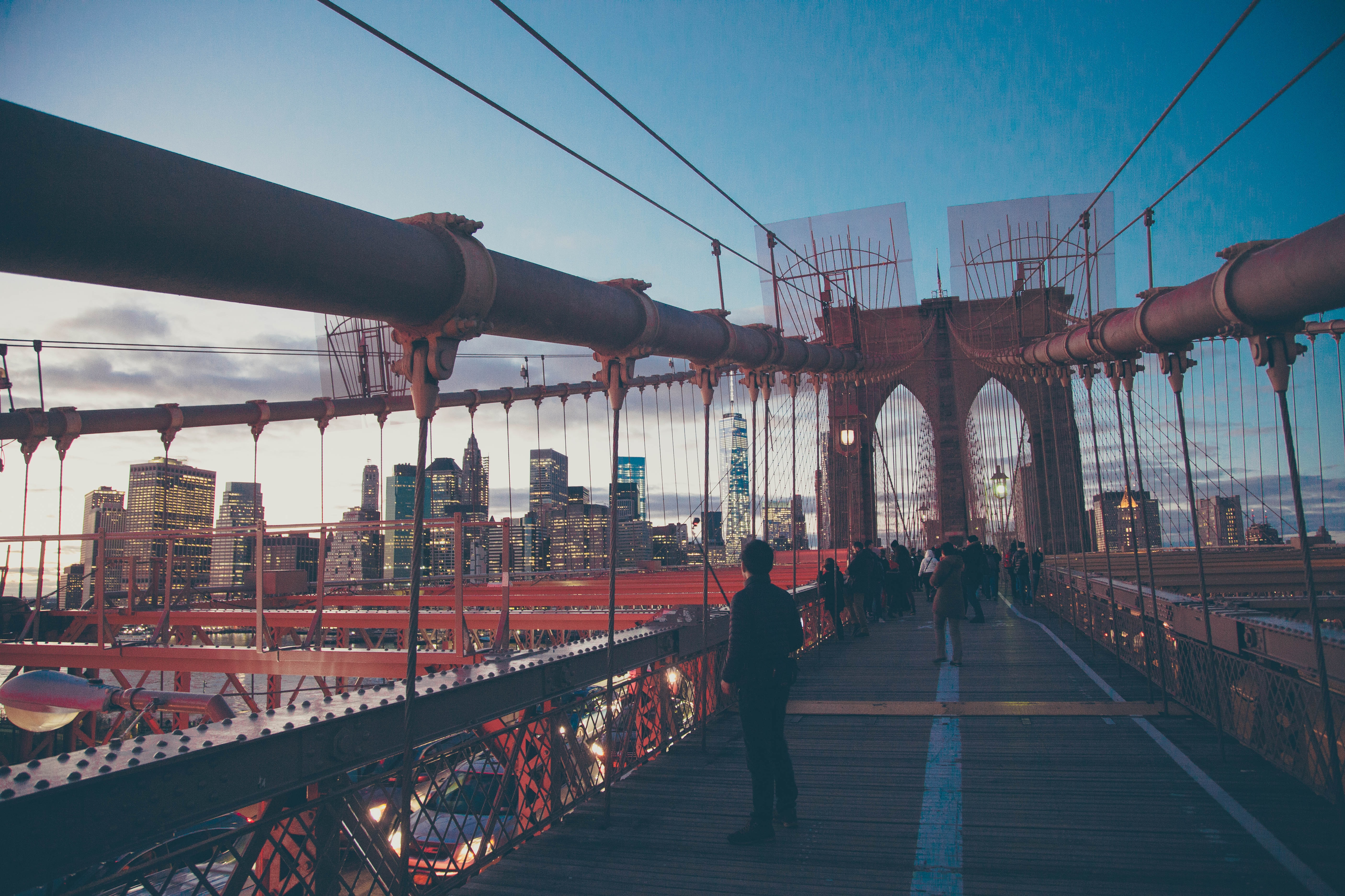 People walking along the Brooklyn Bridge in New York City at dusk