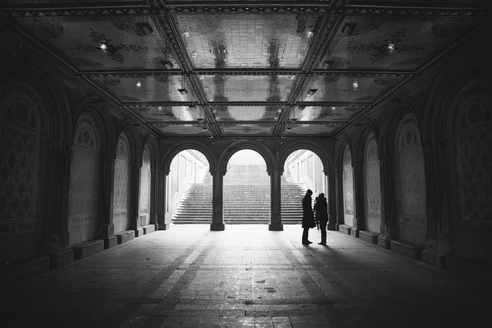 grayscale two people standing on hallway