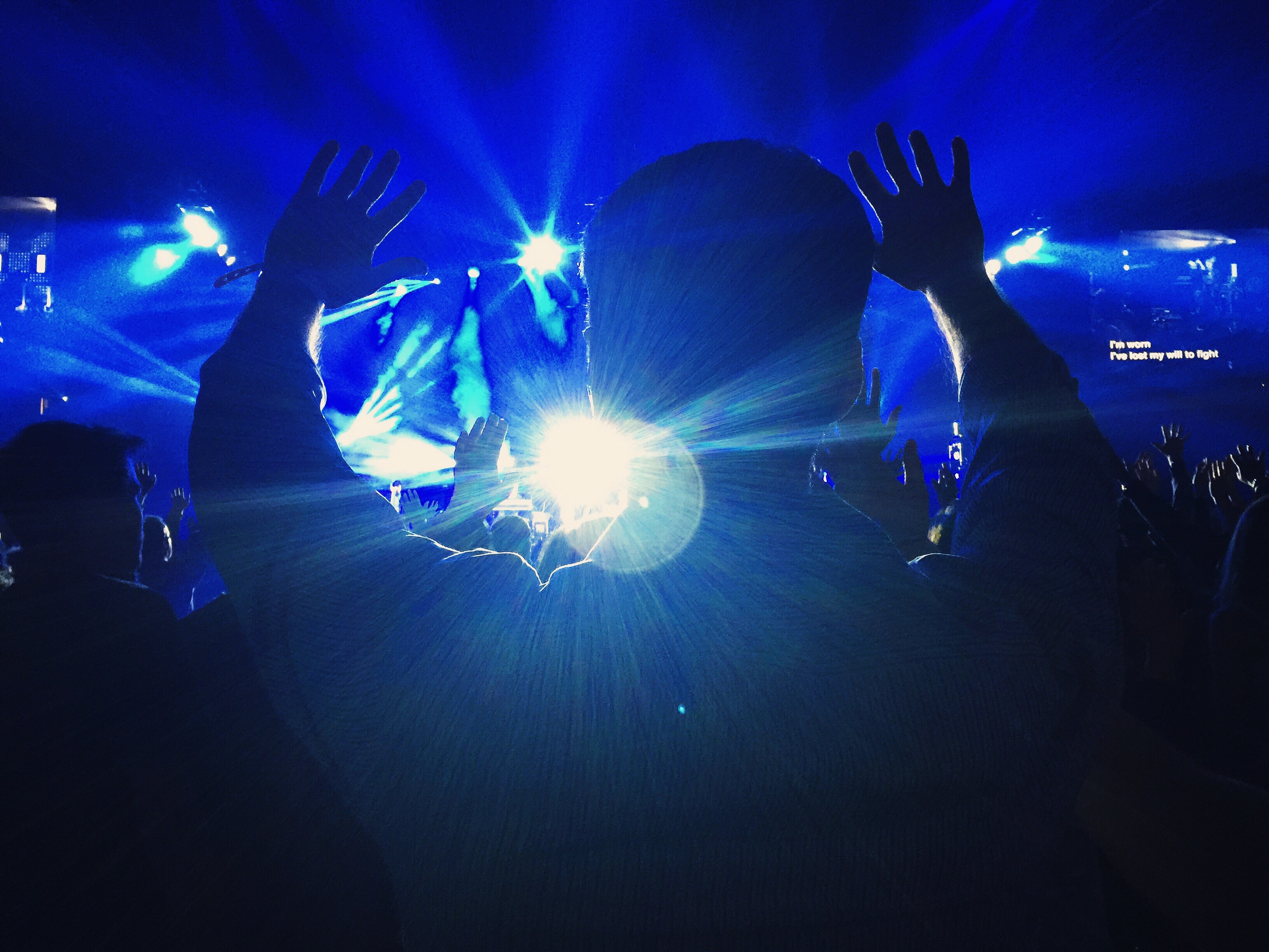 The silhouette of a person at a concert throwing their hands up in the blue light