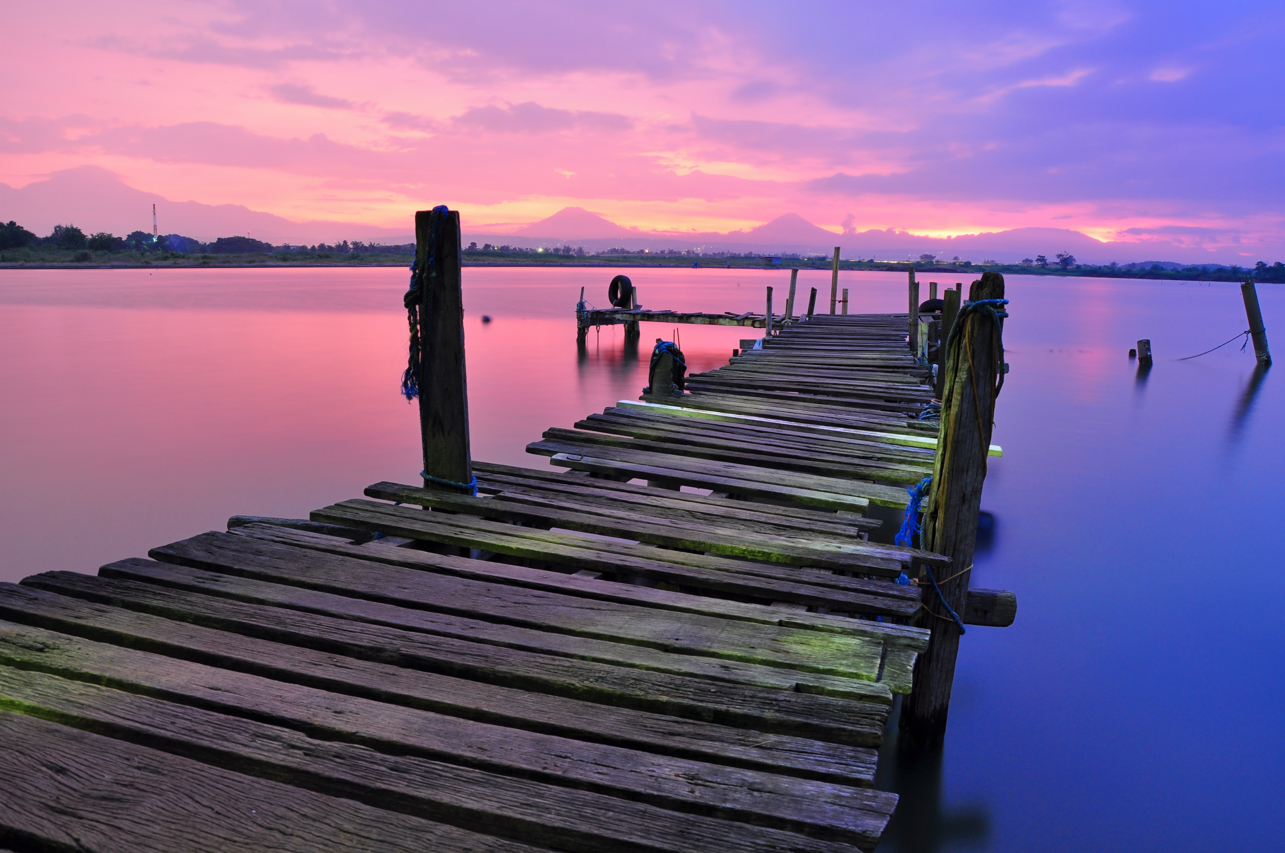 An old dock that is falling apart over the water that is reflecting the pink and purple sky