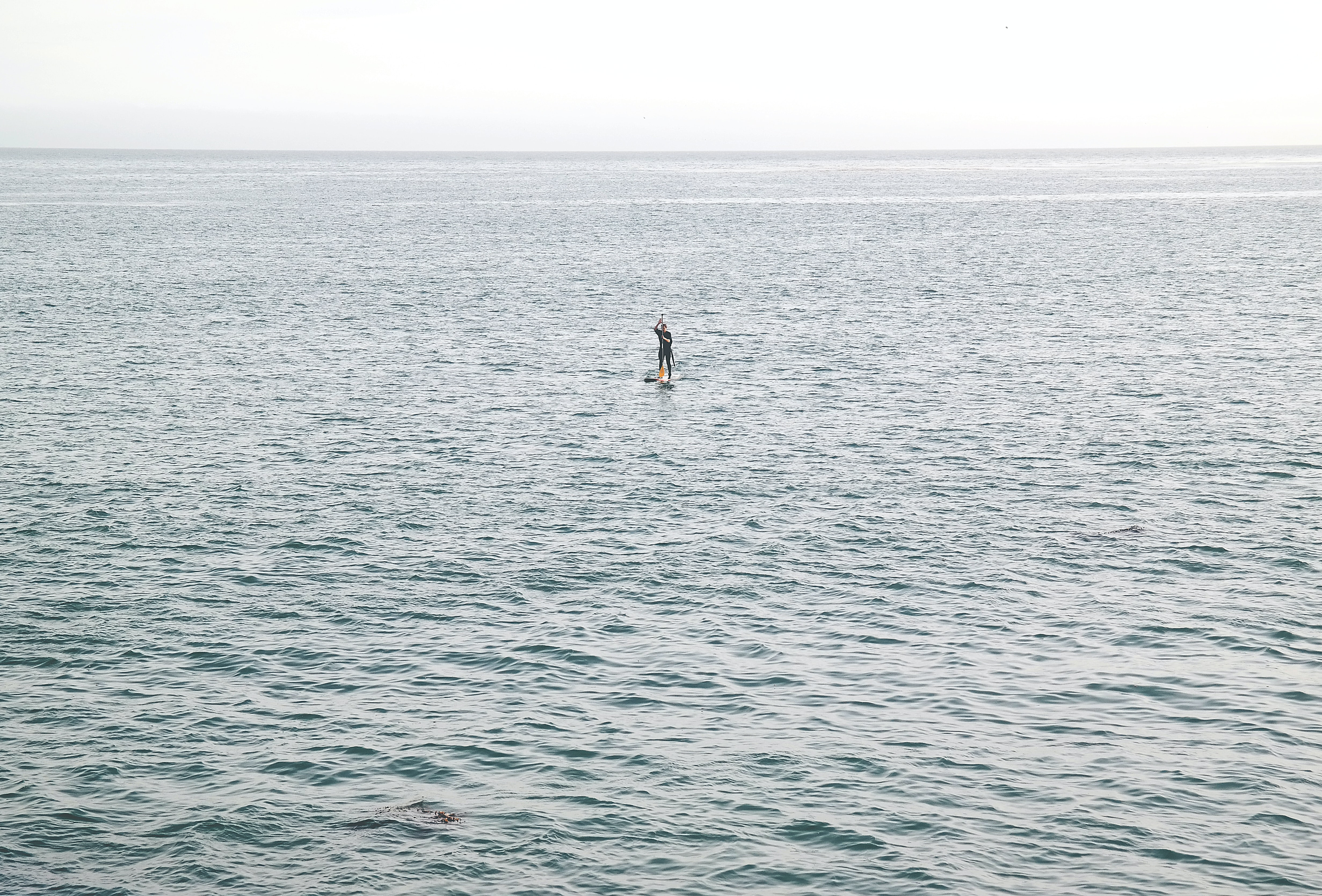 A distant shot of a paddle boarder in a huge mass of tranquil sea