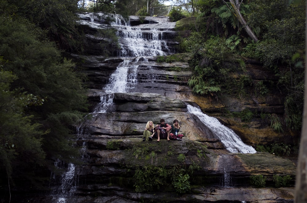 three person sitting on rock formation in waterfalls surrounded with trees at daytime