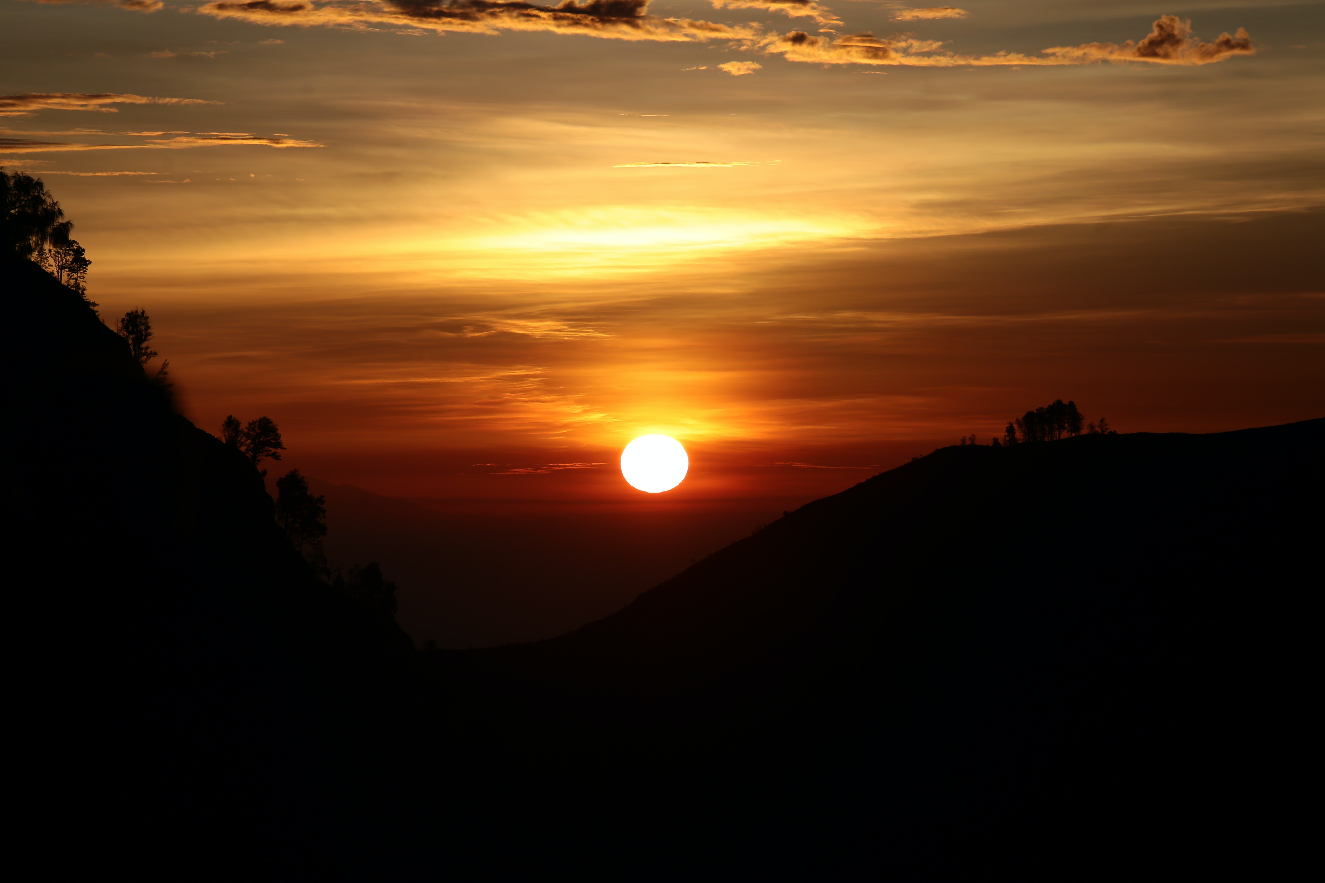 Sun setting over the silhouette of a steep valley
