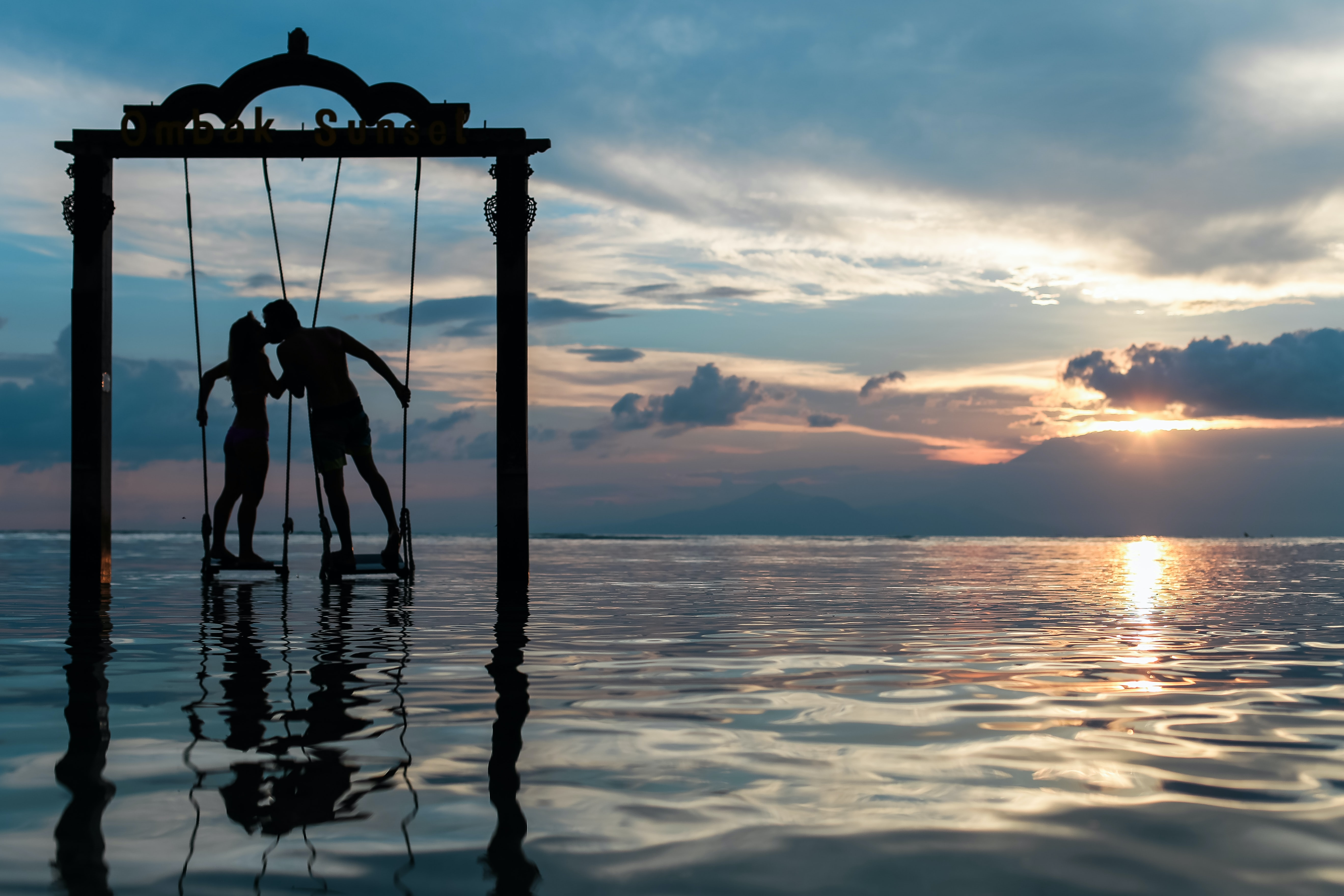 Lovers kiss on a tropical ocean swing at sunset