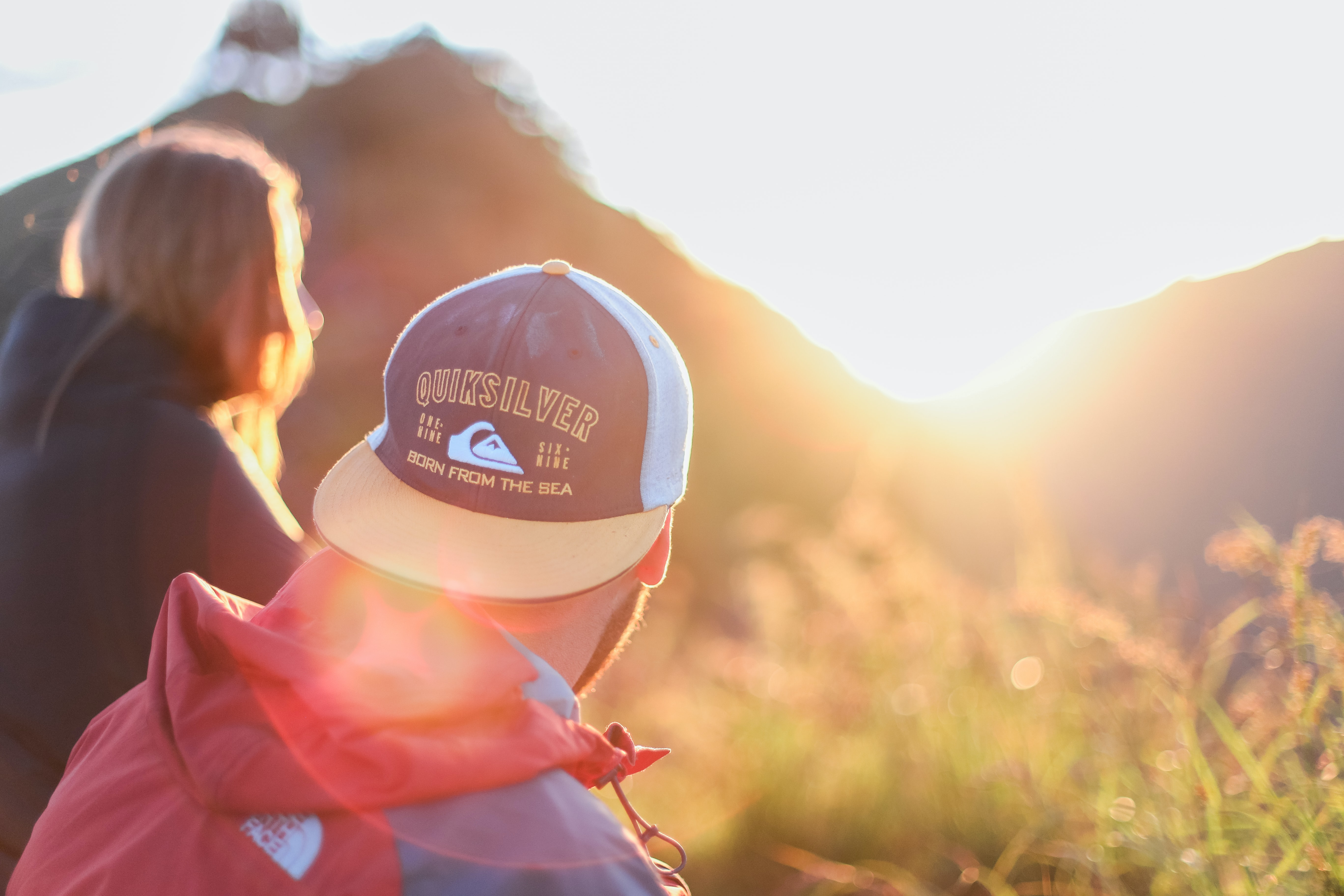 A guy wearing a Quicksilver hat and Northface jacket watching the sunset