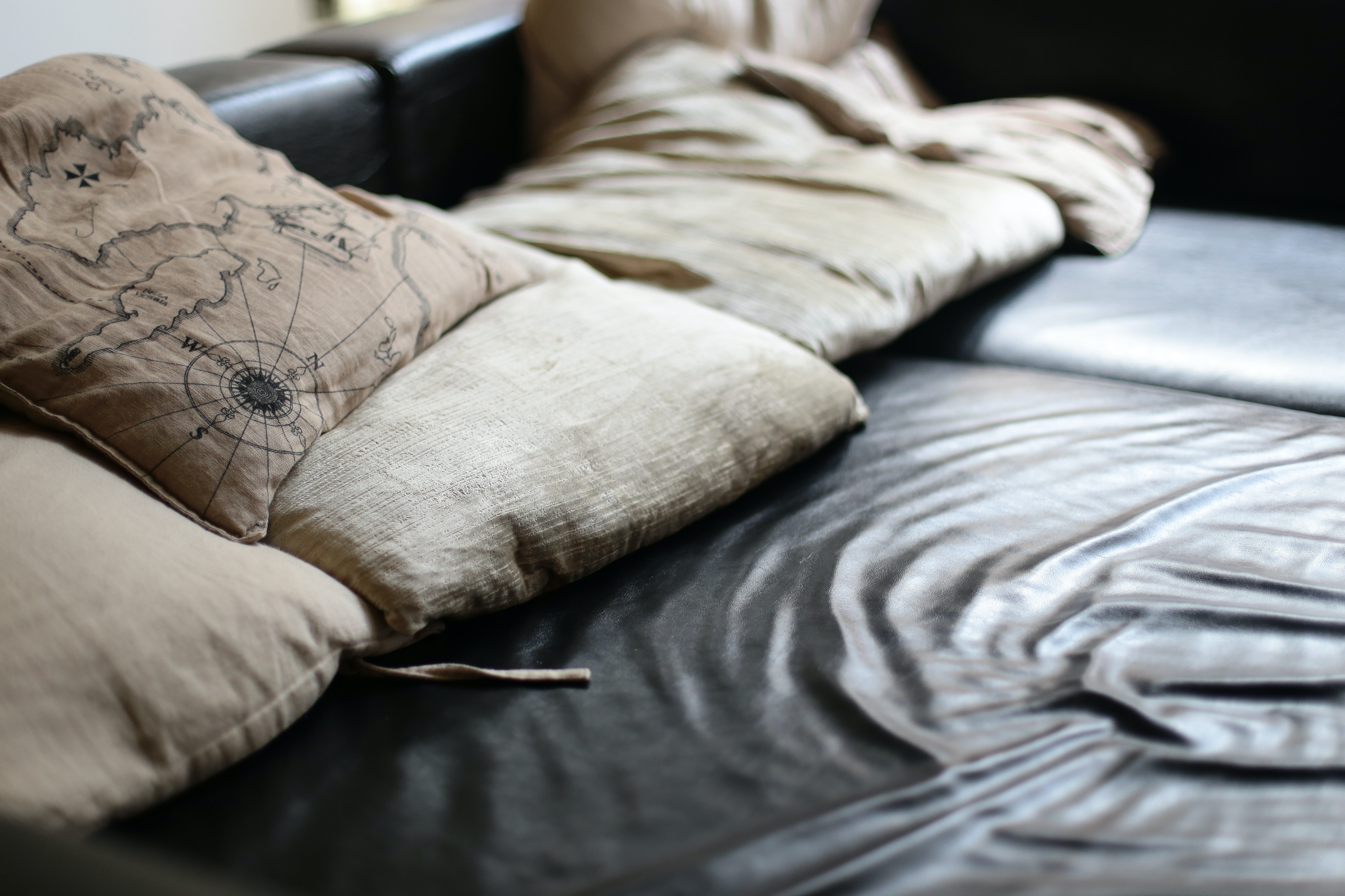 A leather couch with beige pillows and pillows with a map on it