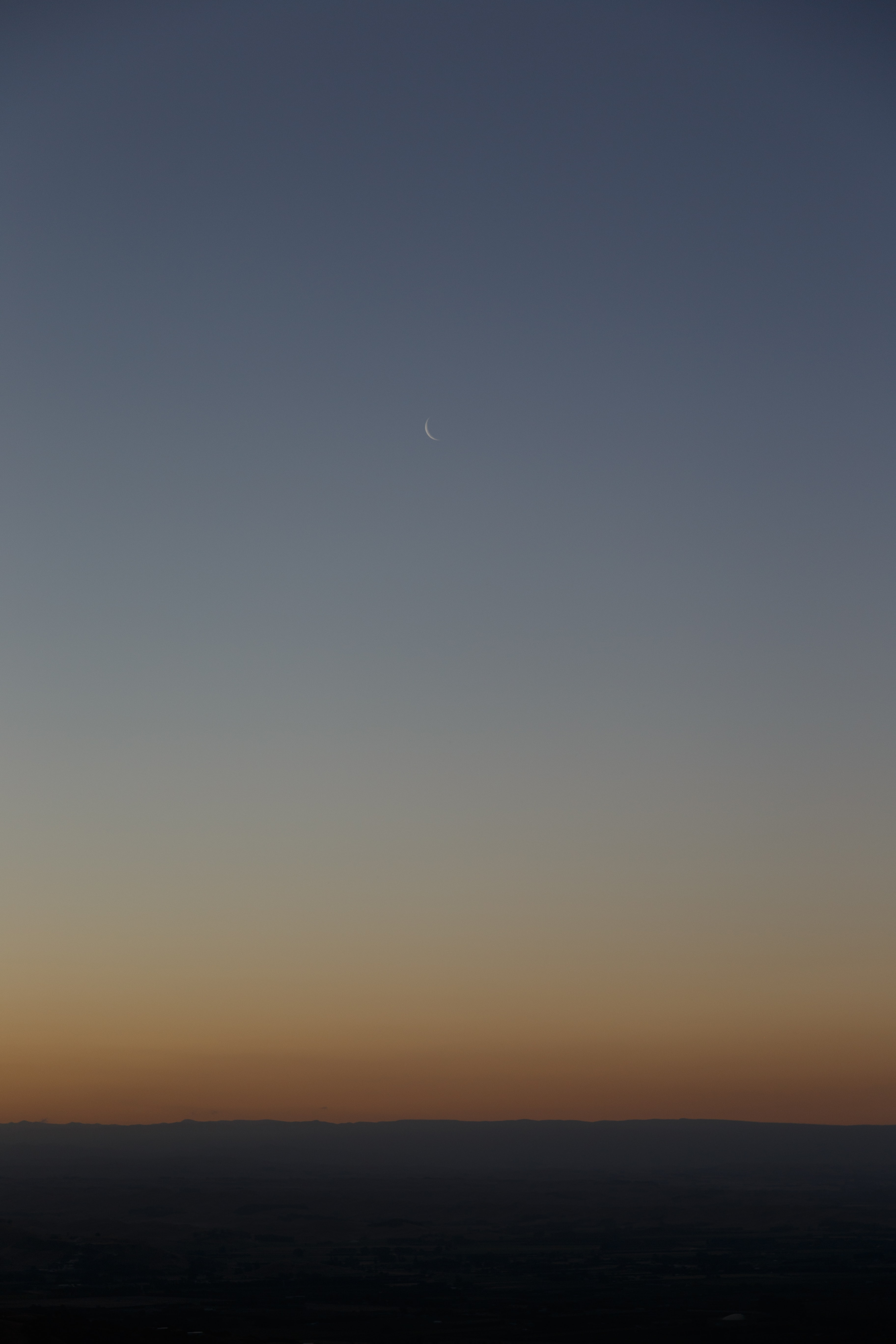 brown and blue horizon with crescent moon