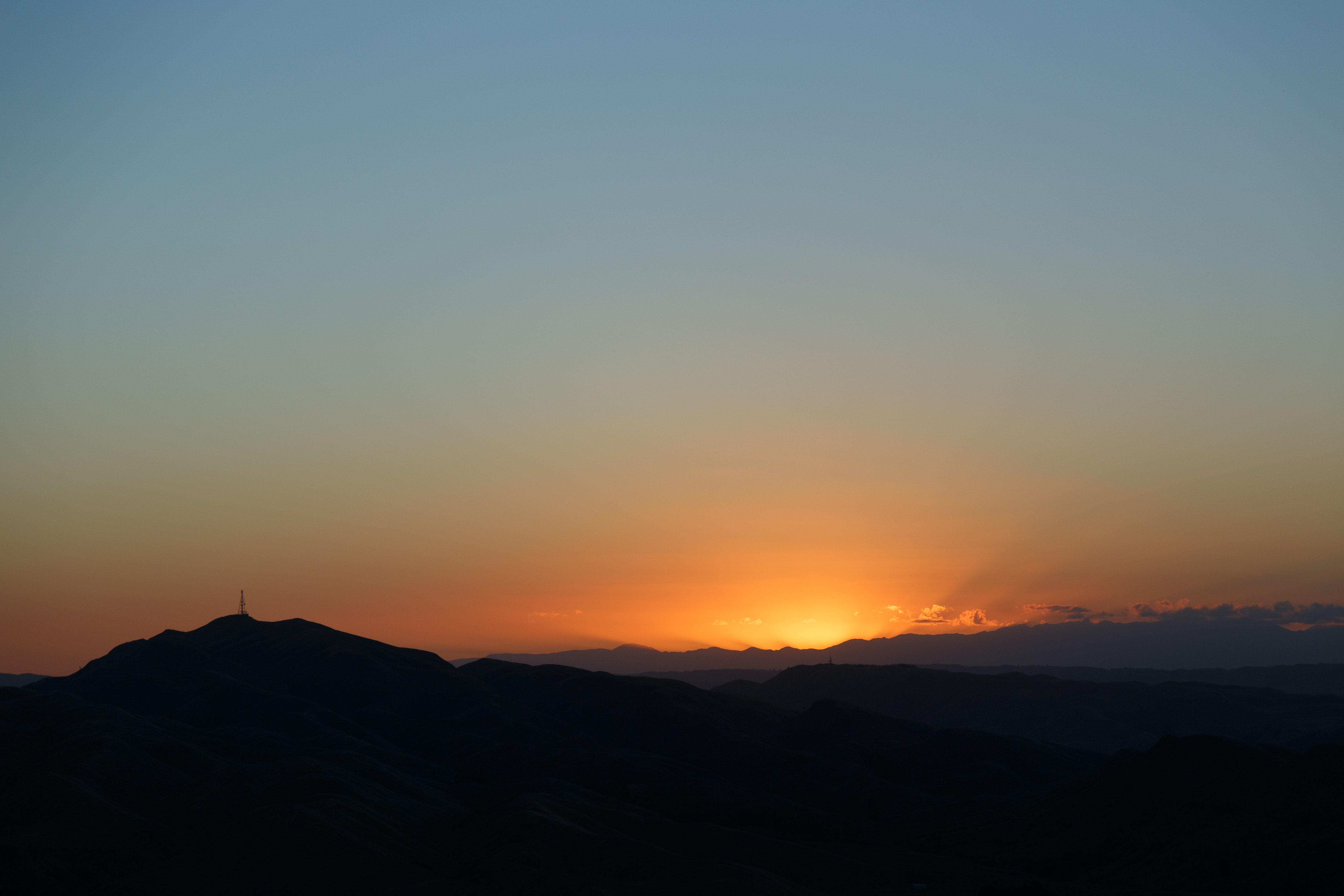 Low golden sunset with the sun behind mountains.