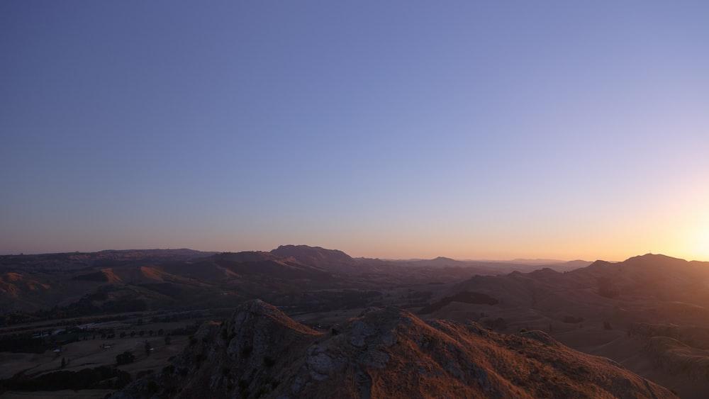 brown hills under blue sky during sunrise