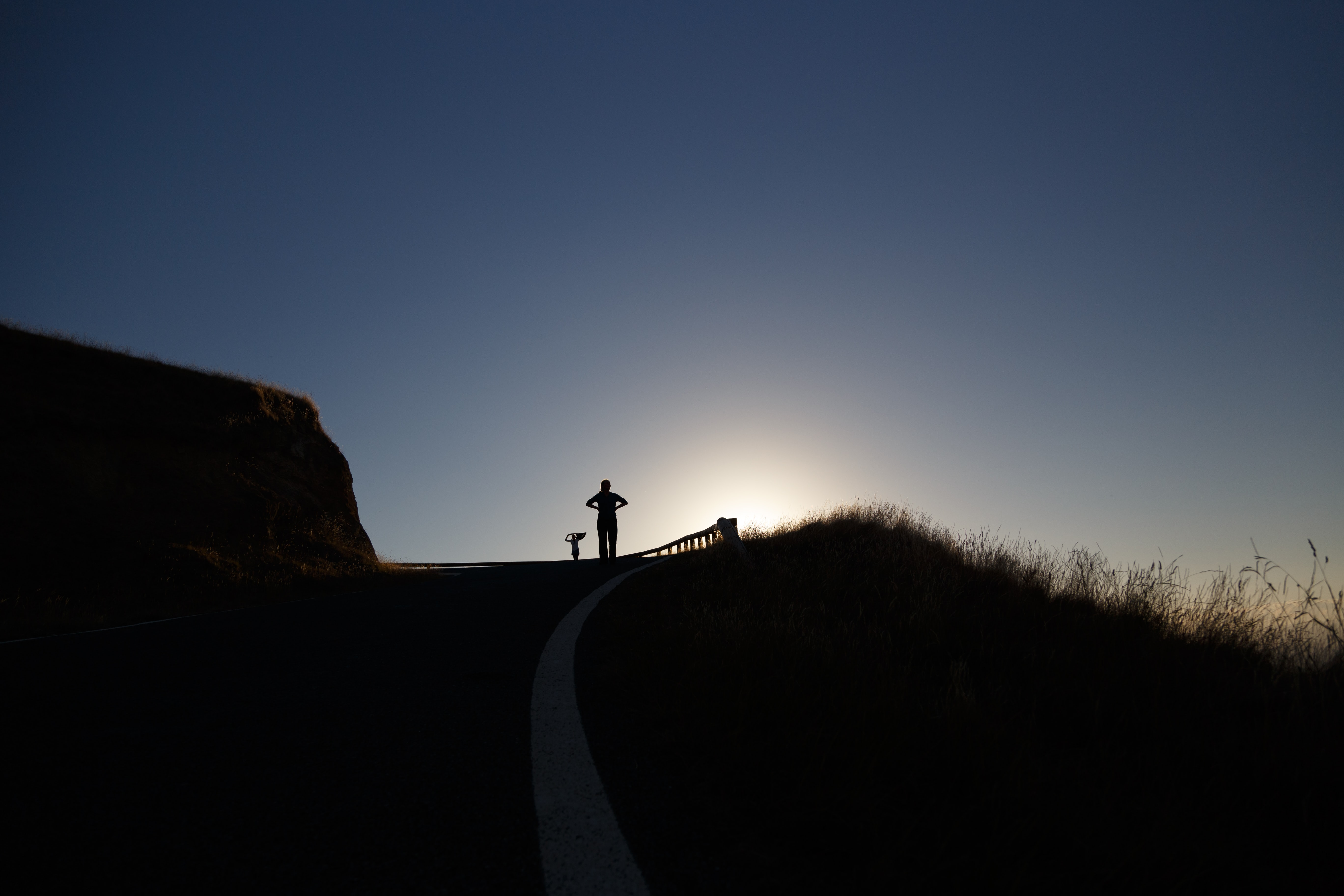 Silhouette of a person standing proudly atop a hill at sunrise