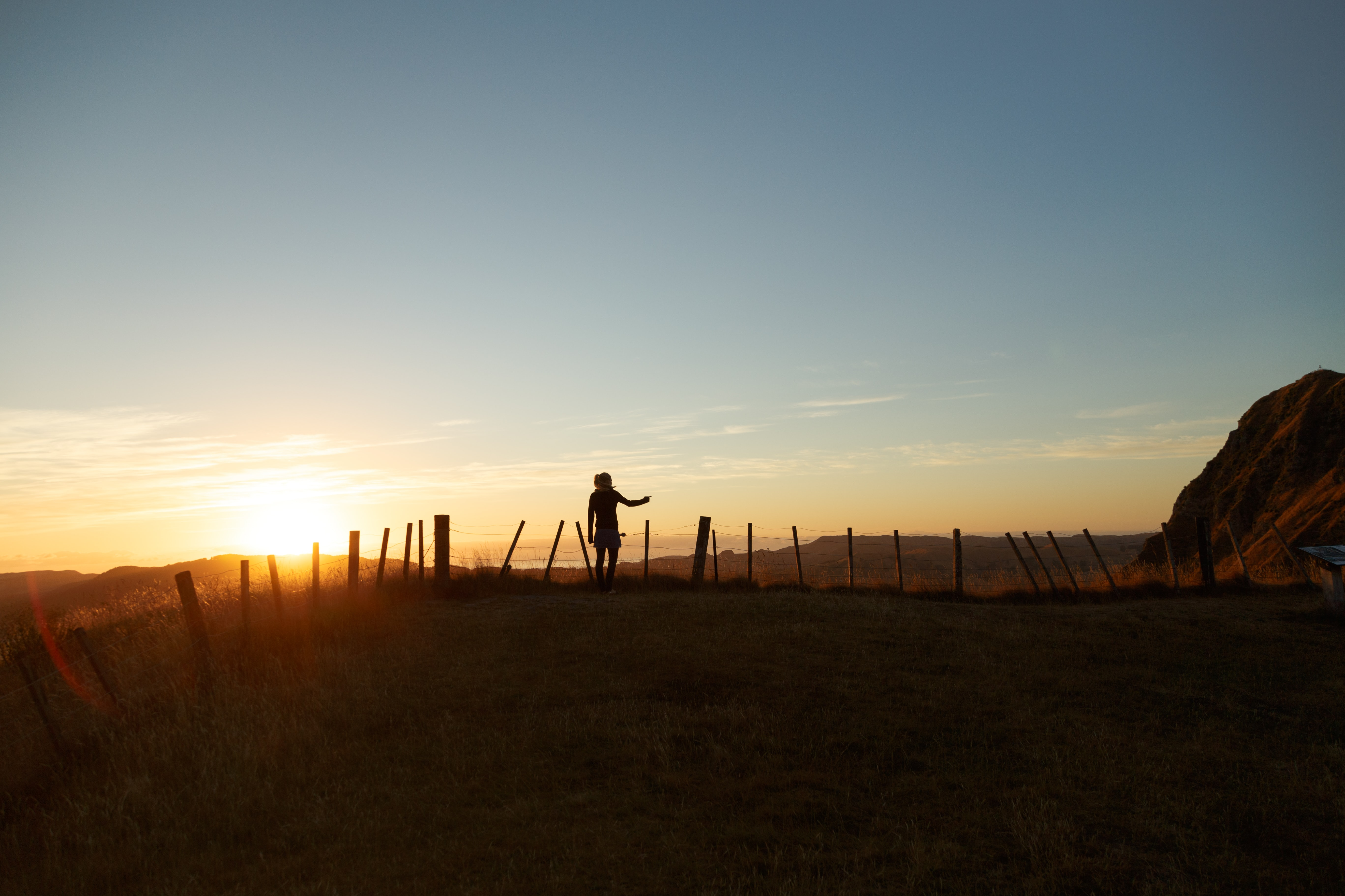 A silhouette of a woman extending her hand next to a wire fence during sunset