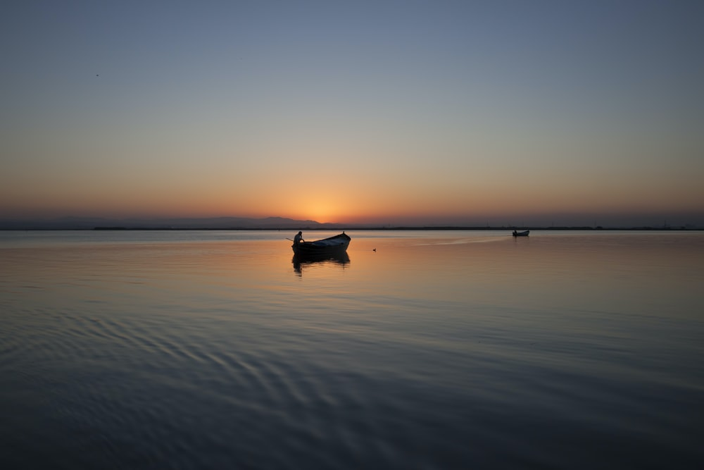silhouette of boat on body of water during golden hour