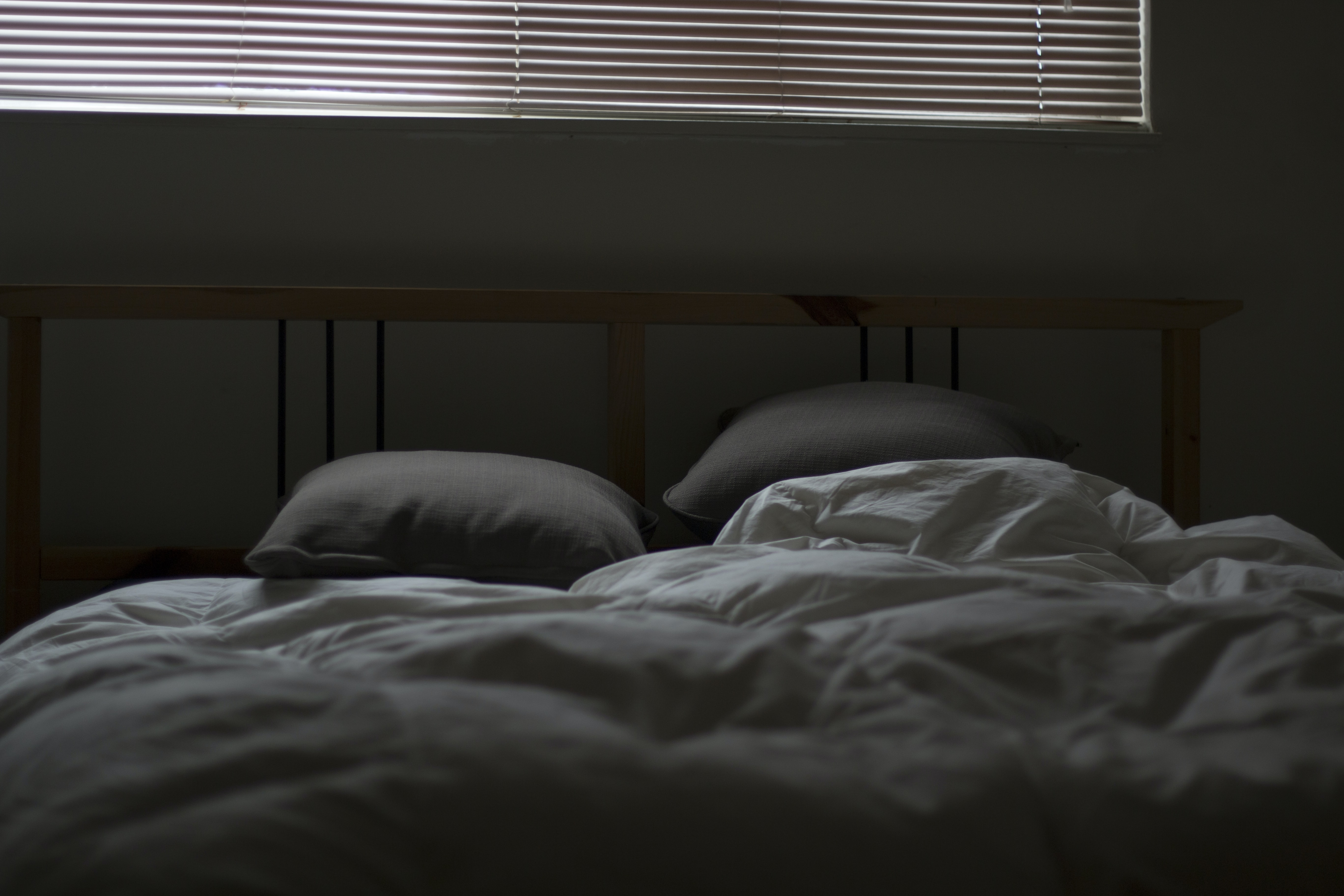 Ruffled gray covers and sheets with two pillows and a large window with blinds above it