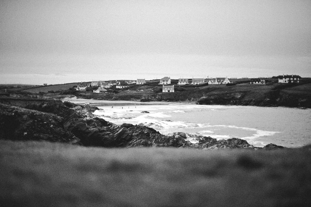grayscale photography of houses beside river