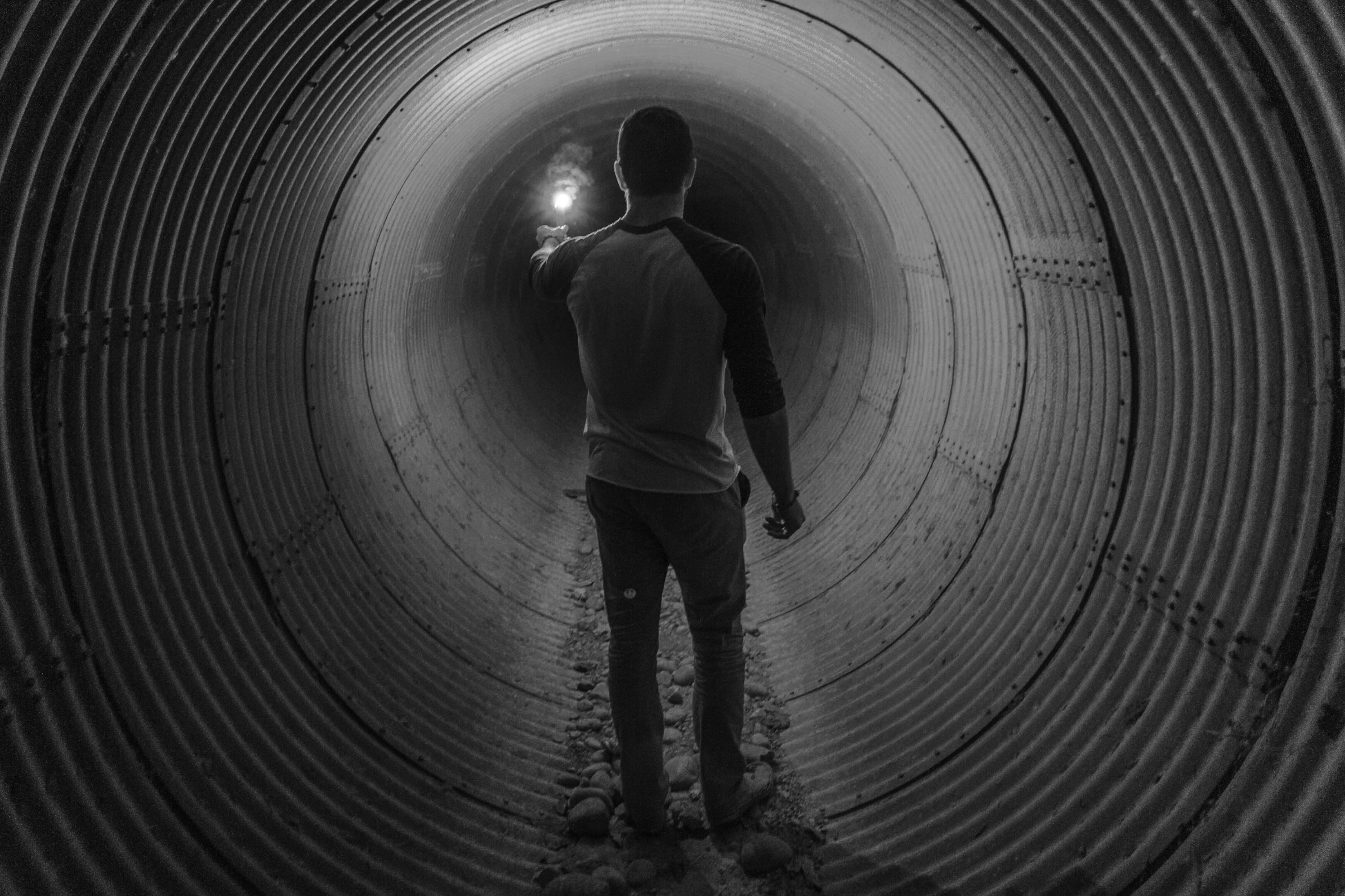 man holding light walking inside tunnel