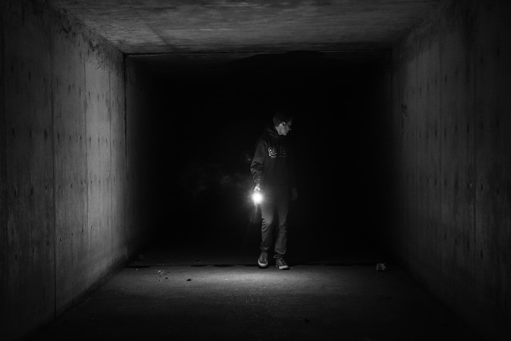 grayscale photography of person walking on tunnel