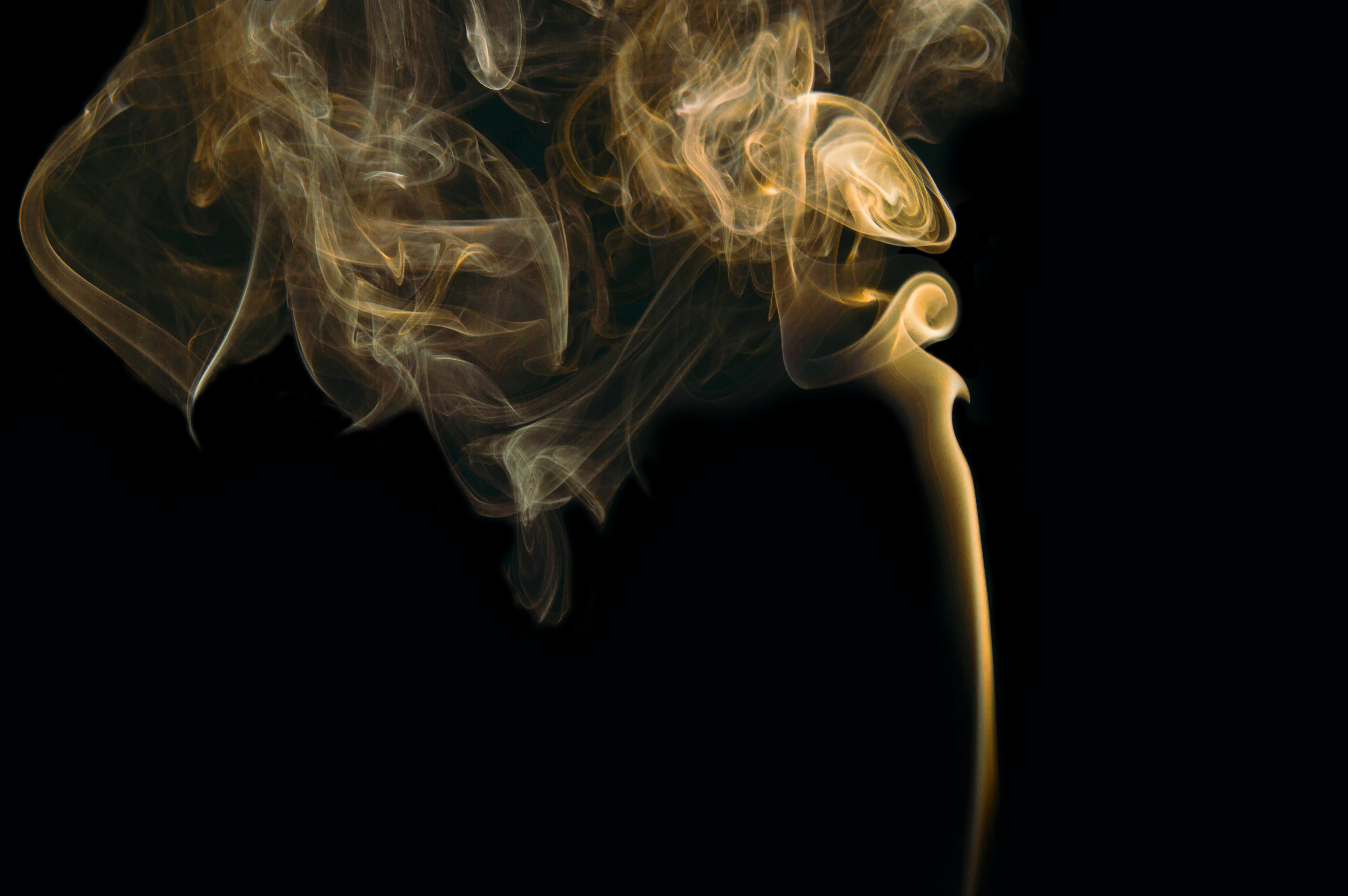 Orangish yellow smoke curling into light with a black background