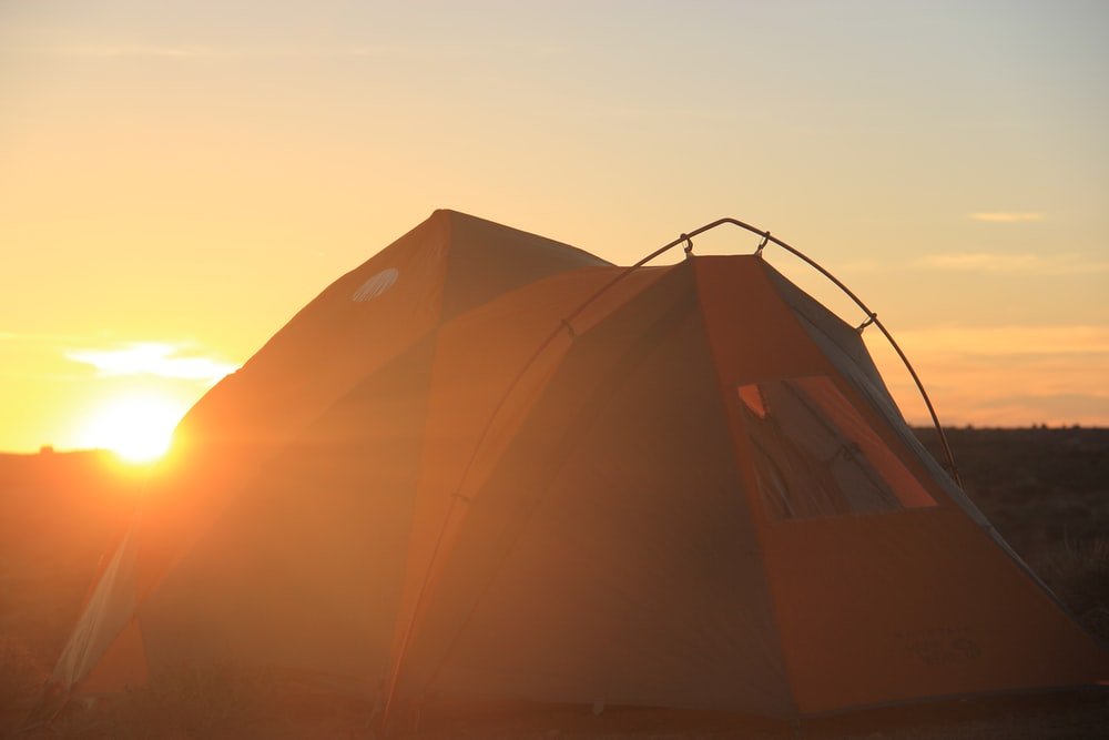 brown tent under gray sky during sunset