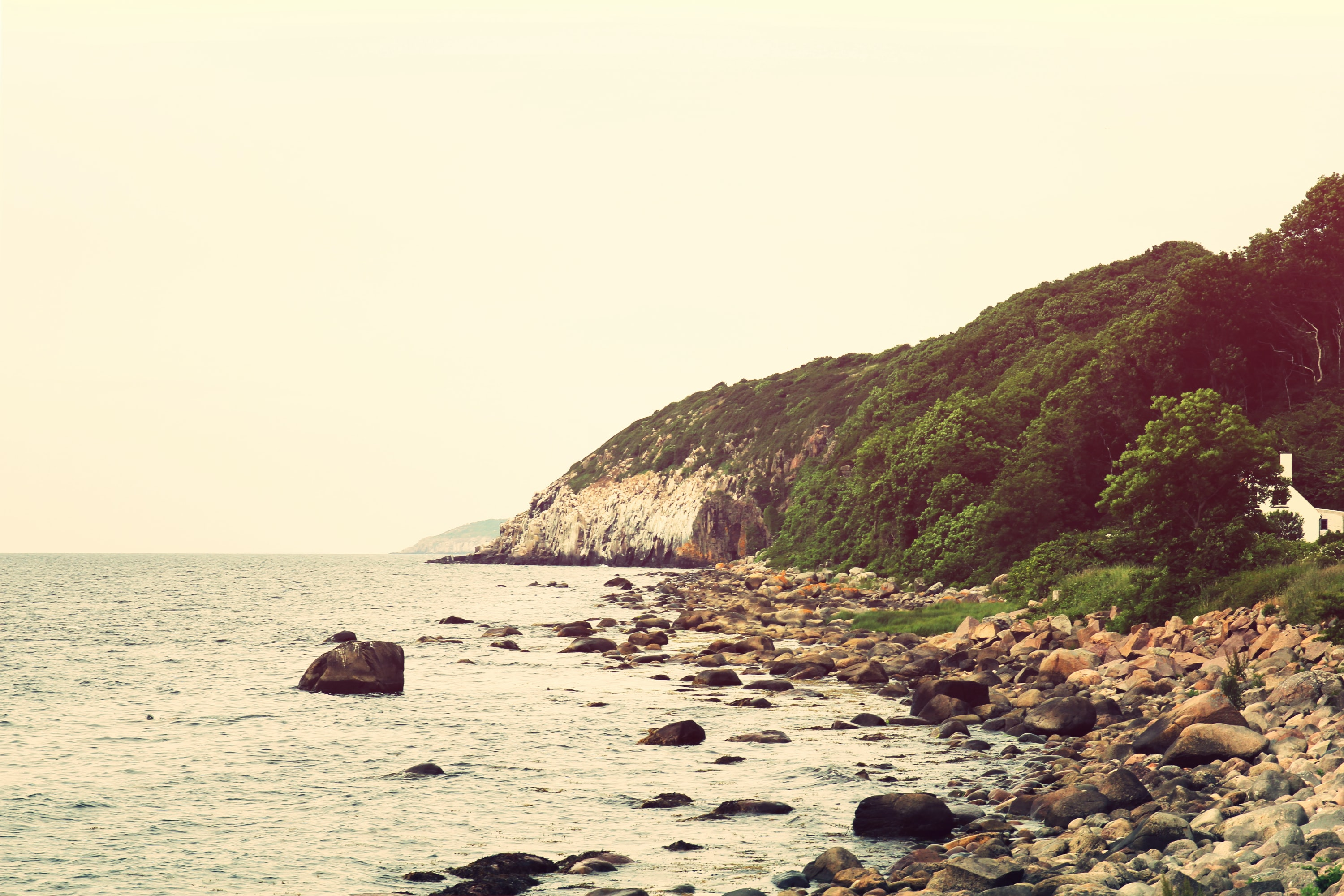 A rocky beach and a white wooded cliff in Bornholm