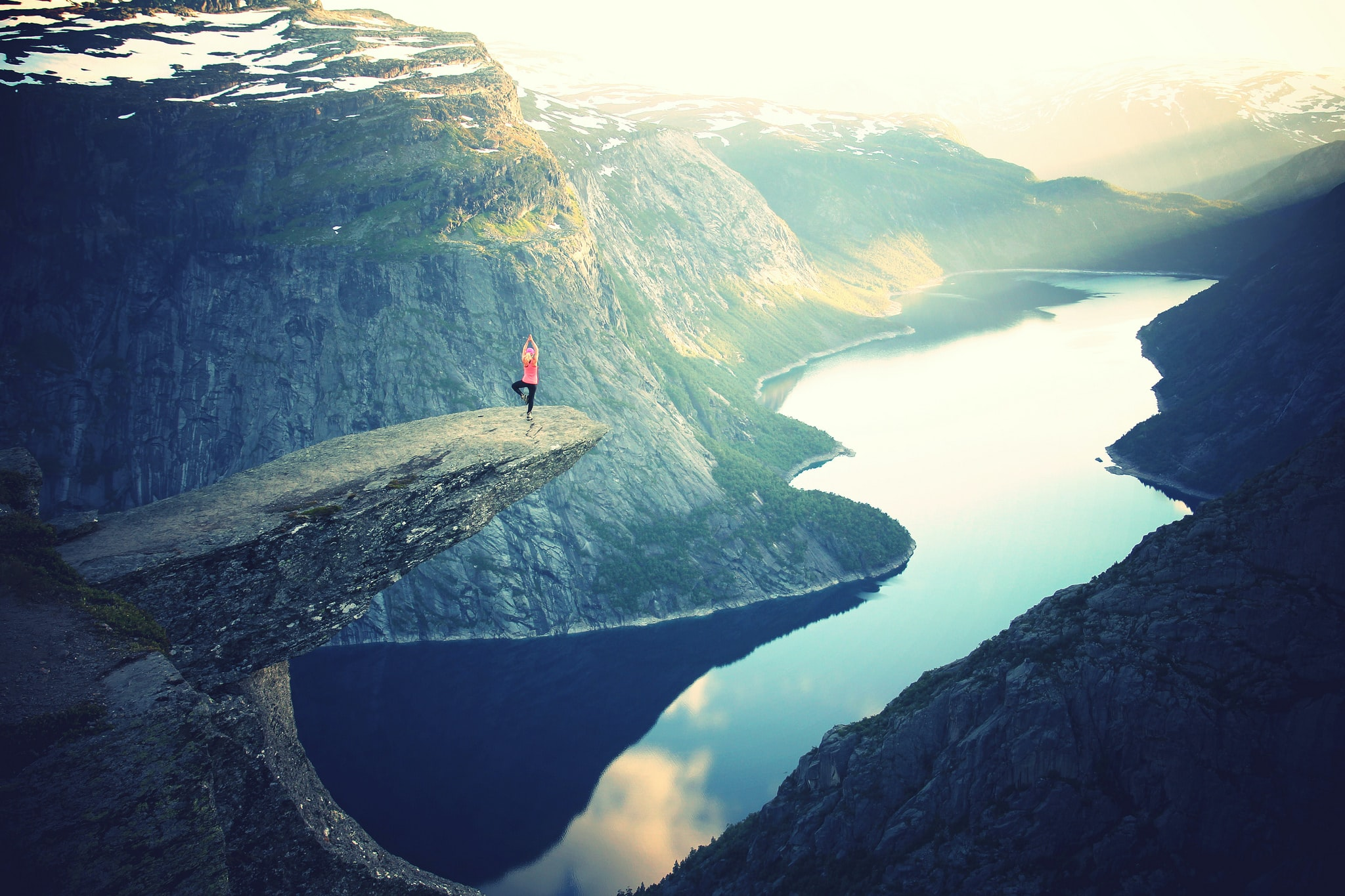 person doing yoga at the trolltunga cliff