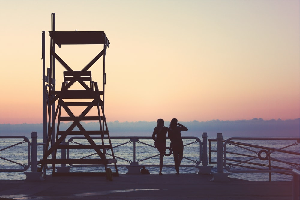 silhouette of two woman beside lifeguard tower