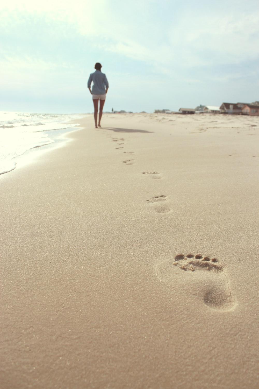 woman wearing blue dress shirt and white short shorts walking on seashore
