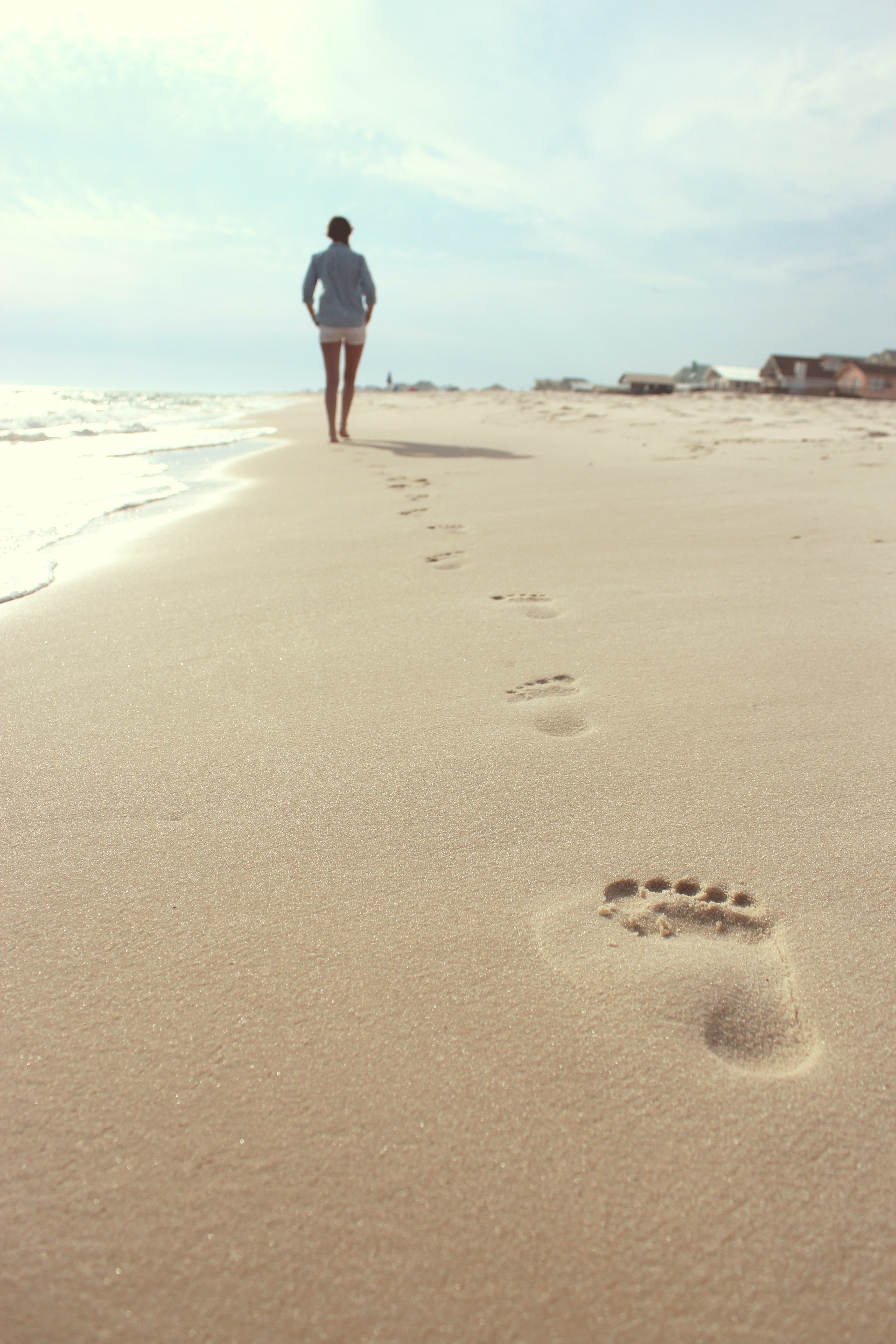 Footsteps of a woman walking on a sand beach