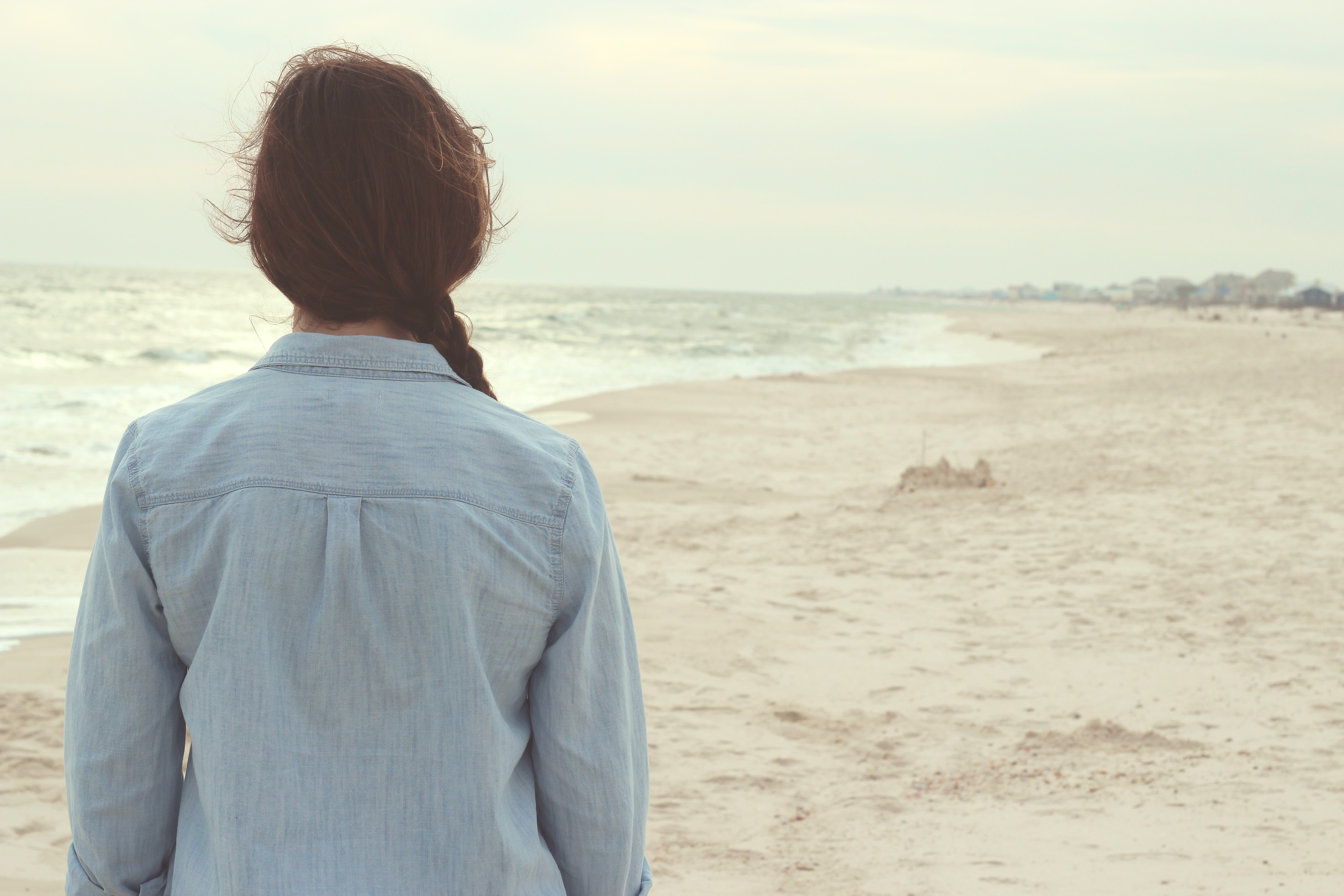 A dark-haired woman looking at a sandy beach