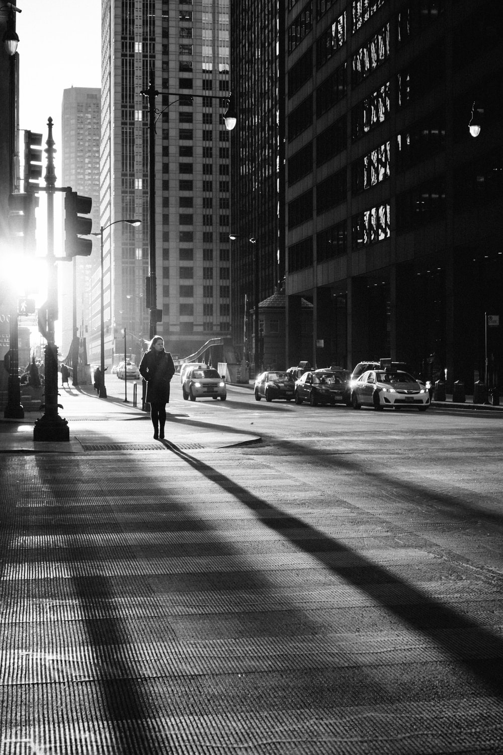 grayscale photo of woman walking on road