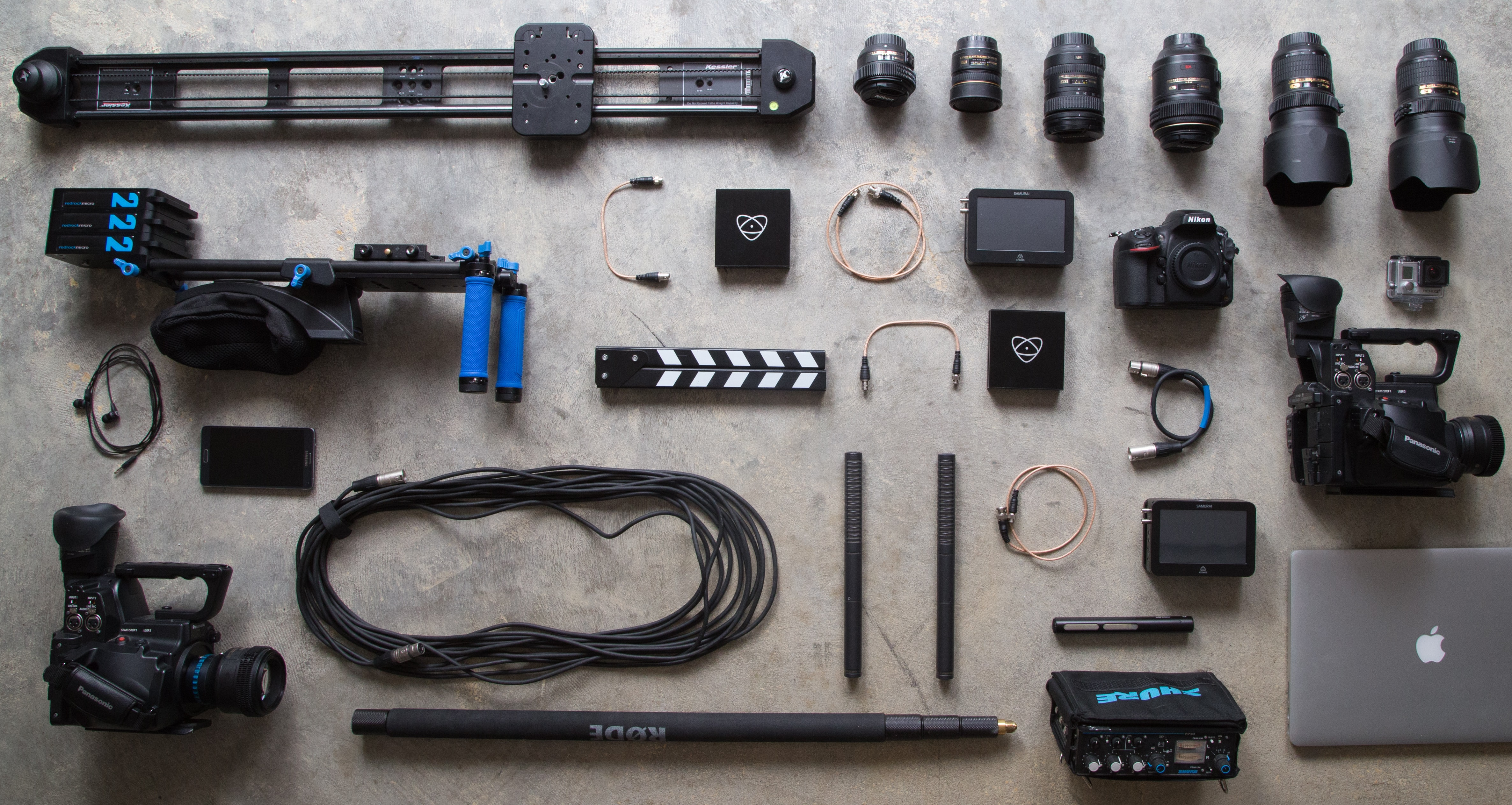 Top down of various camera equipment including cables, receivers, stands, tripods, boom mics, lenses, a camera, headphones, a macbook, a GoPro, a Nikon, and Panasonic video cameras
