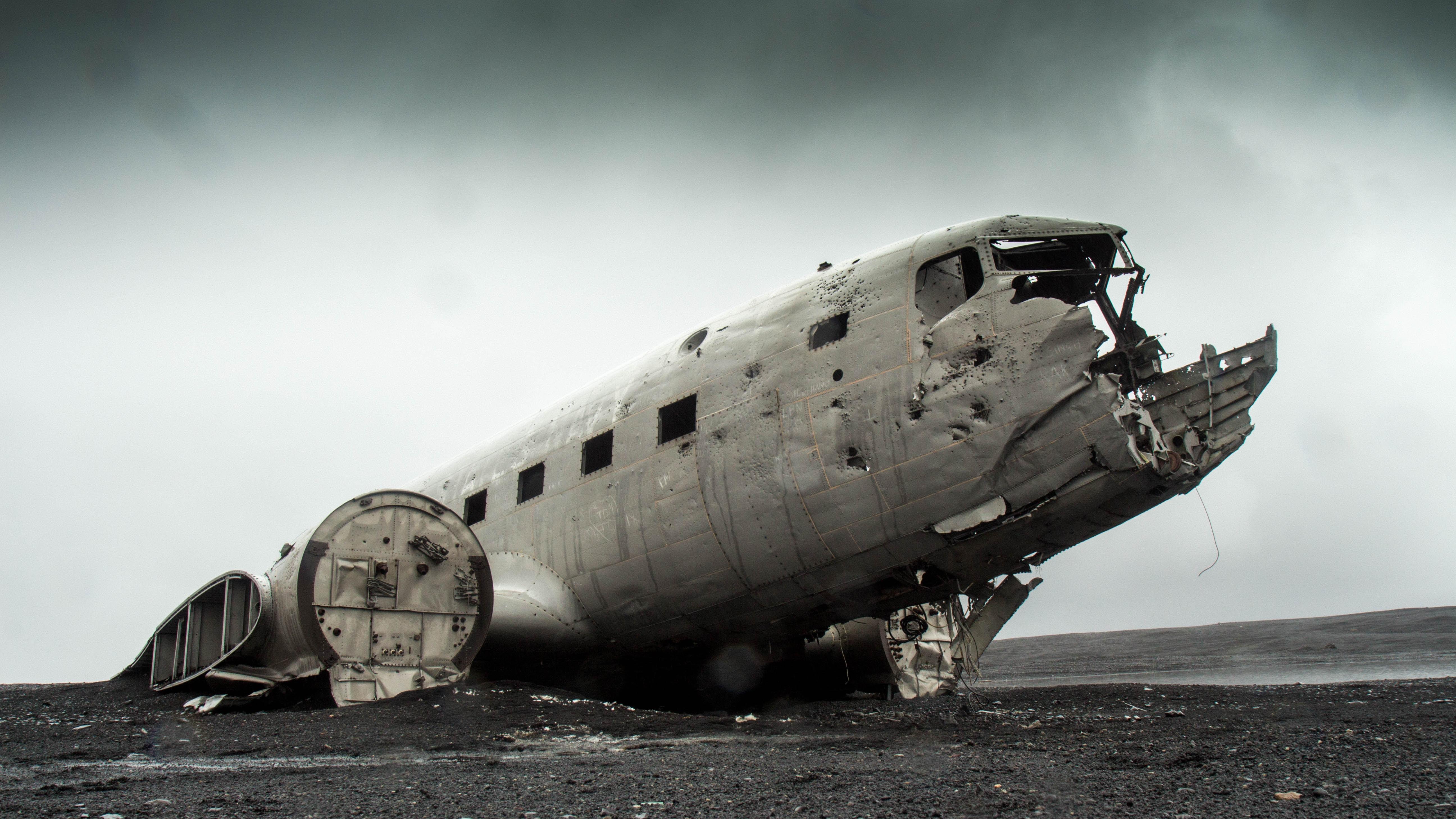 A broken, strange and crashed plane on a sandy floor
