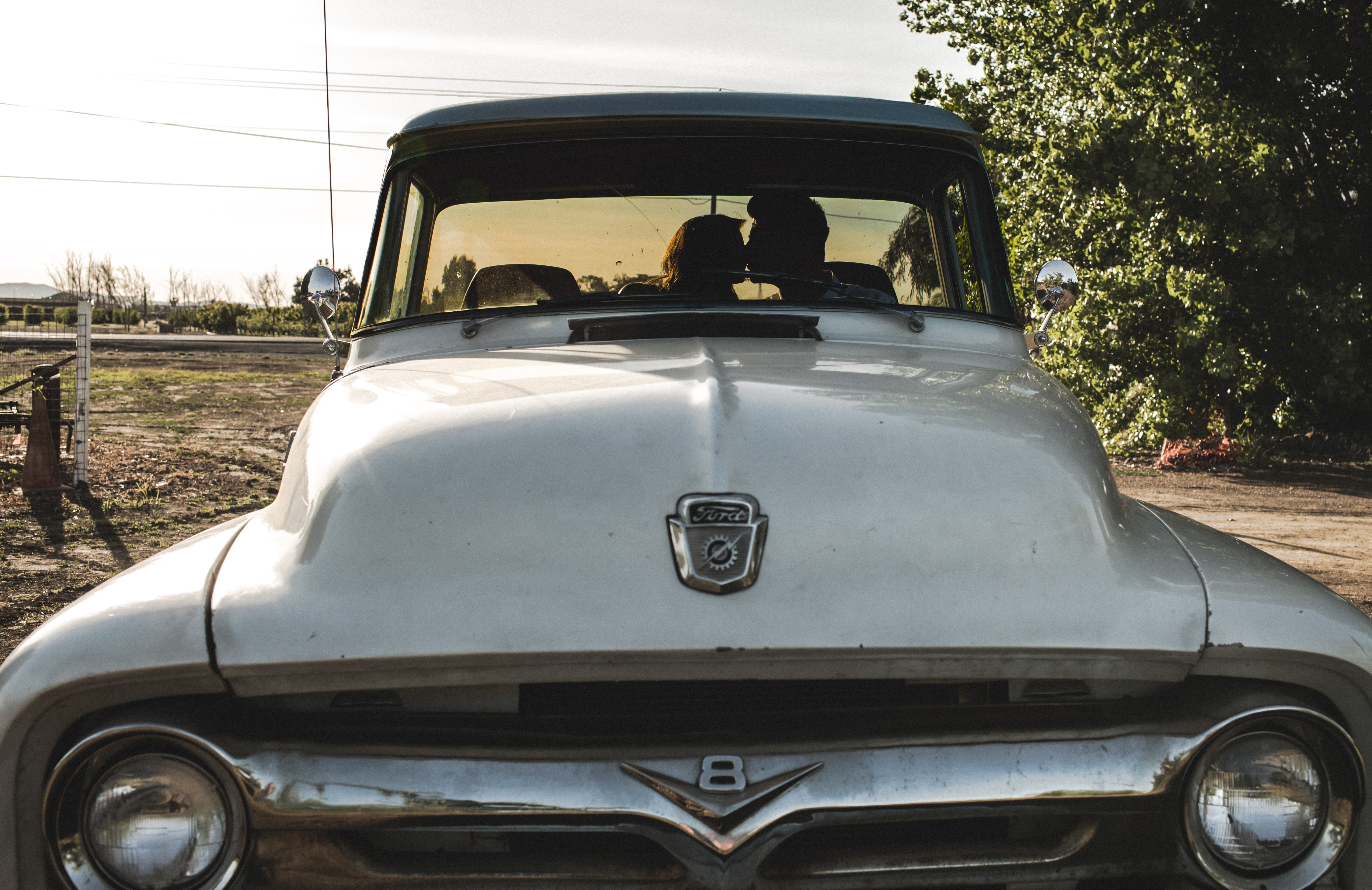 A couple kissing inside an old vintage Ford truck on a farm
