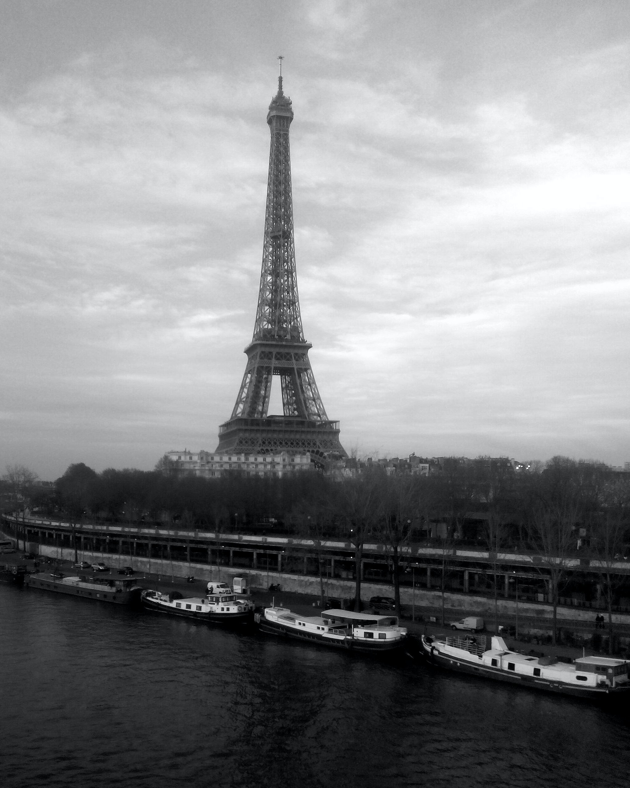Black and white Eiffel Tower with boats along the river