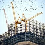 low angle photography of cranes on top of building