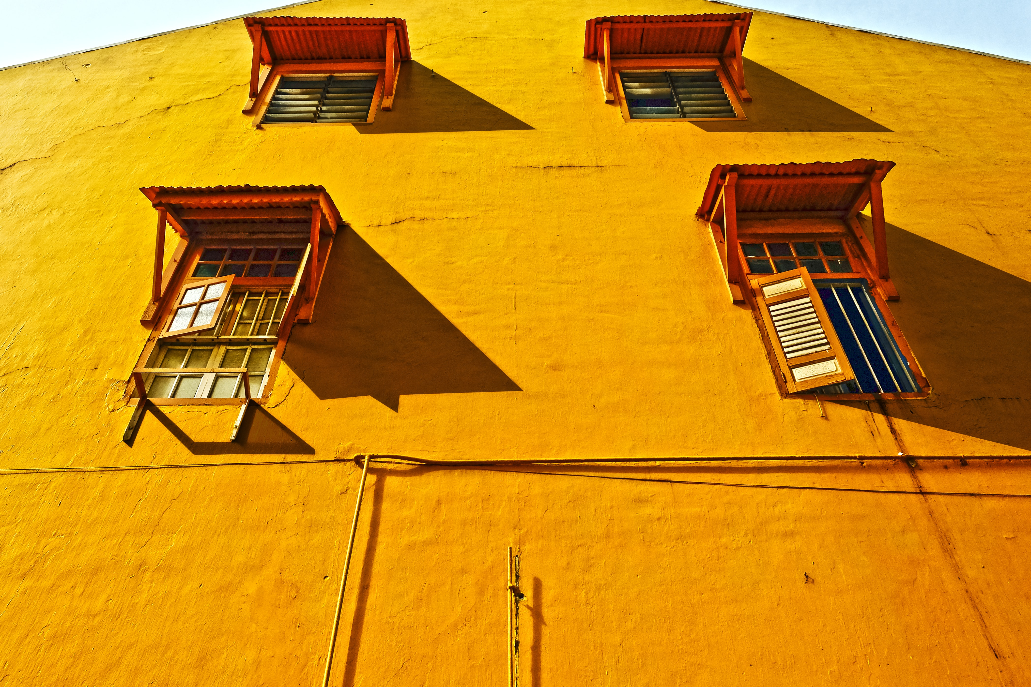 Yellow house wall with four windows and a variety of shutters