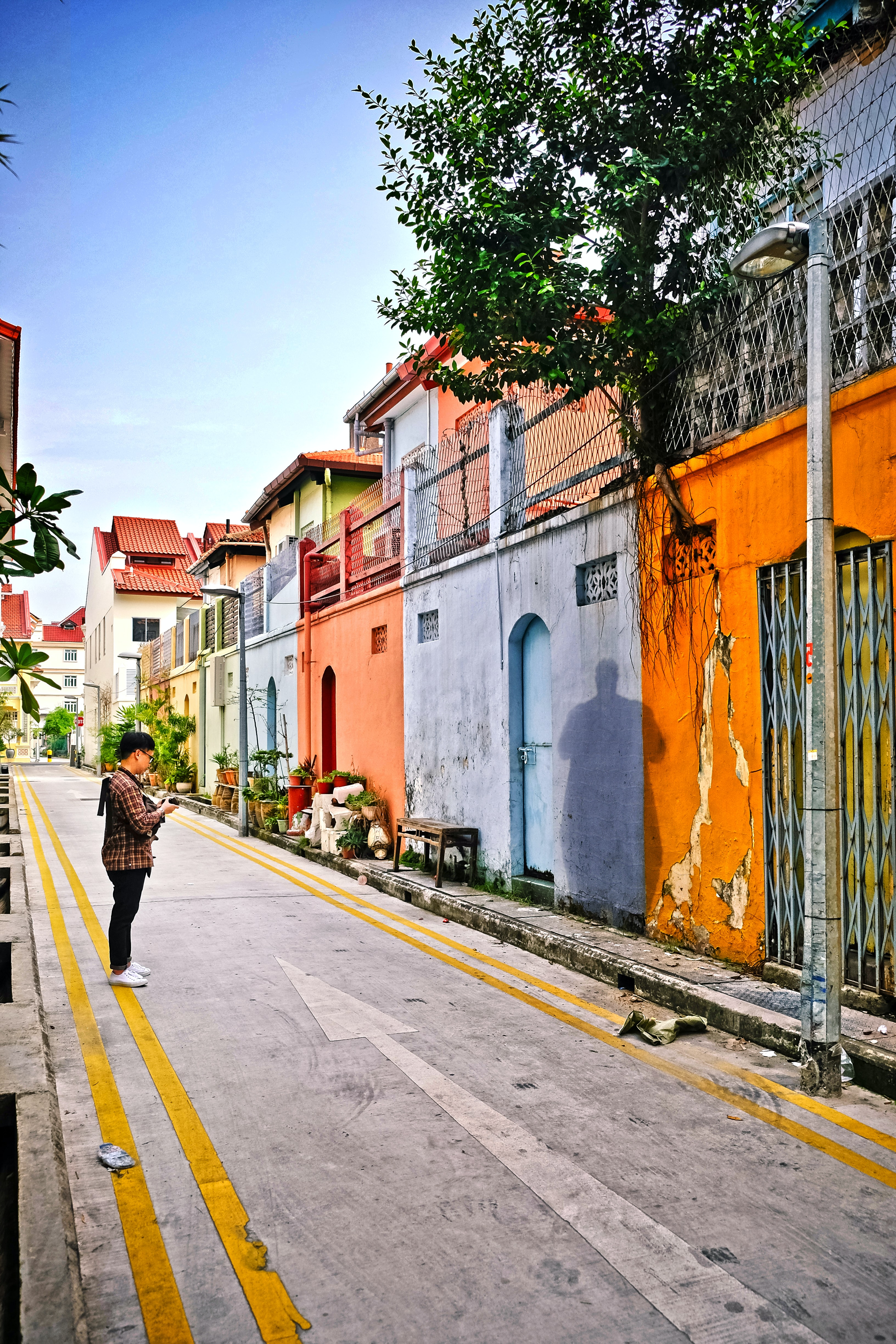 Street view of colorful Asian houses and a man in the street taking pictures