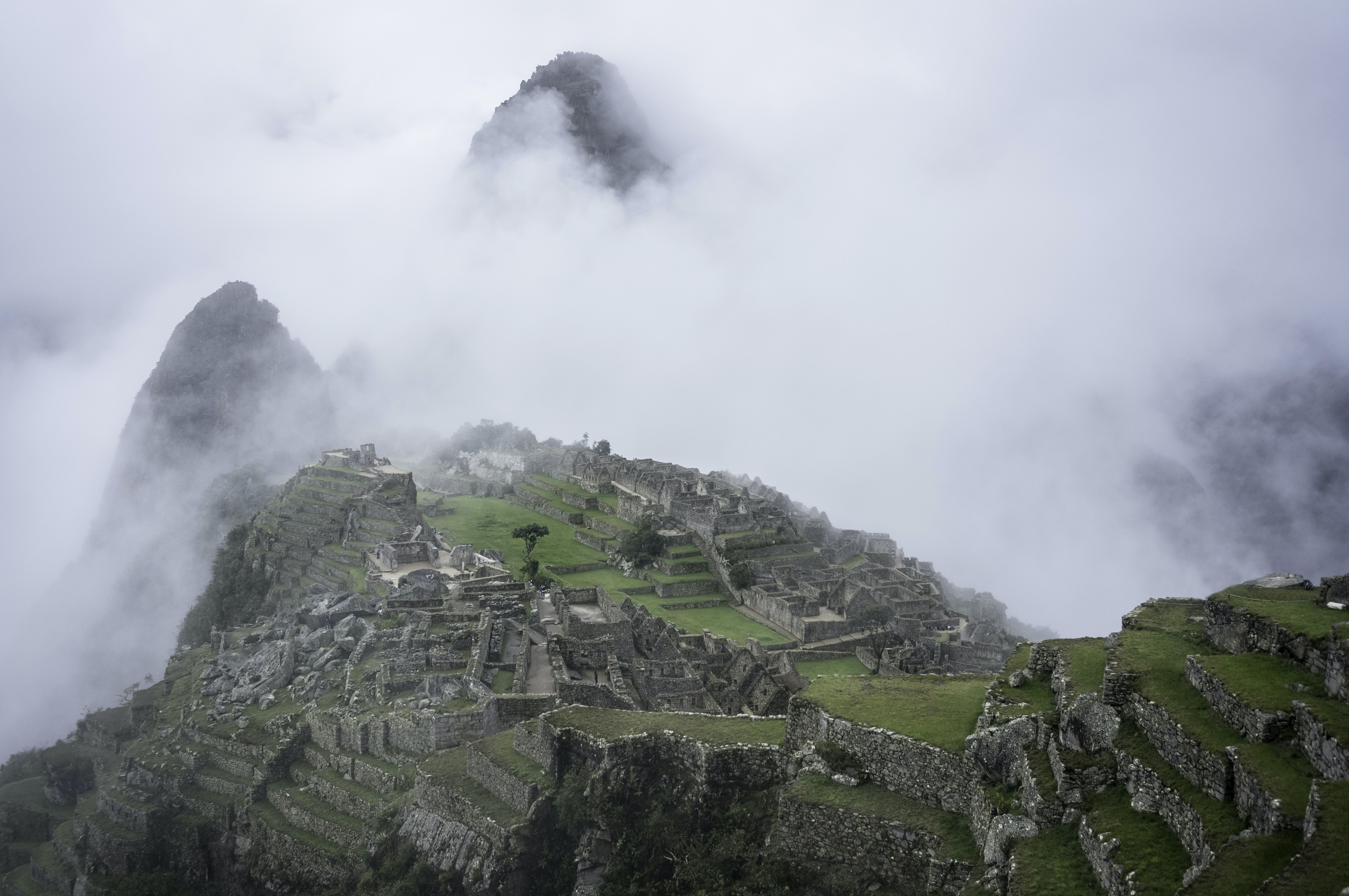 Fog setting over the Machu Picchu ruins on a cool day