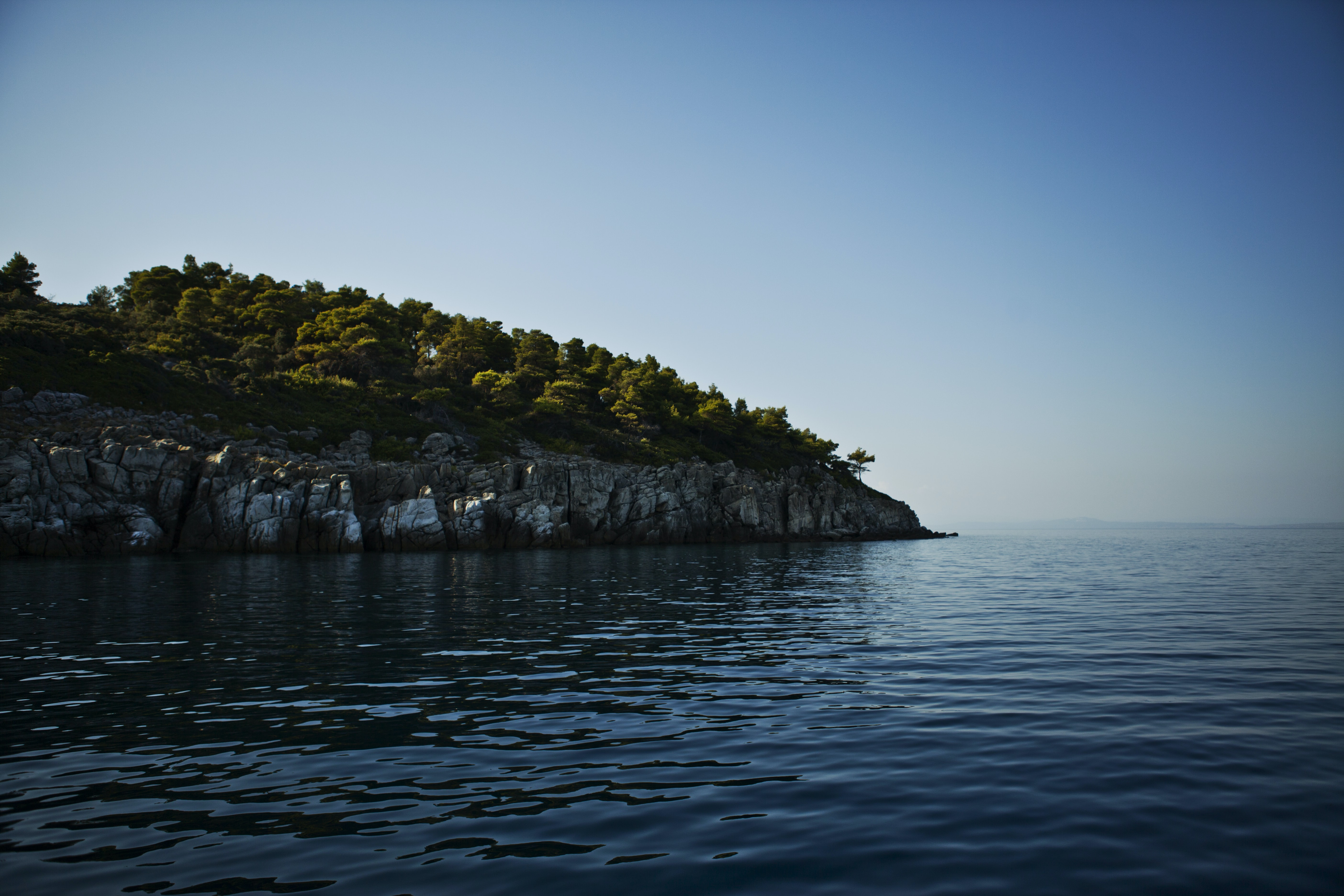 A jagged cliff covered with trees by a vast body of water