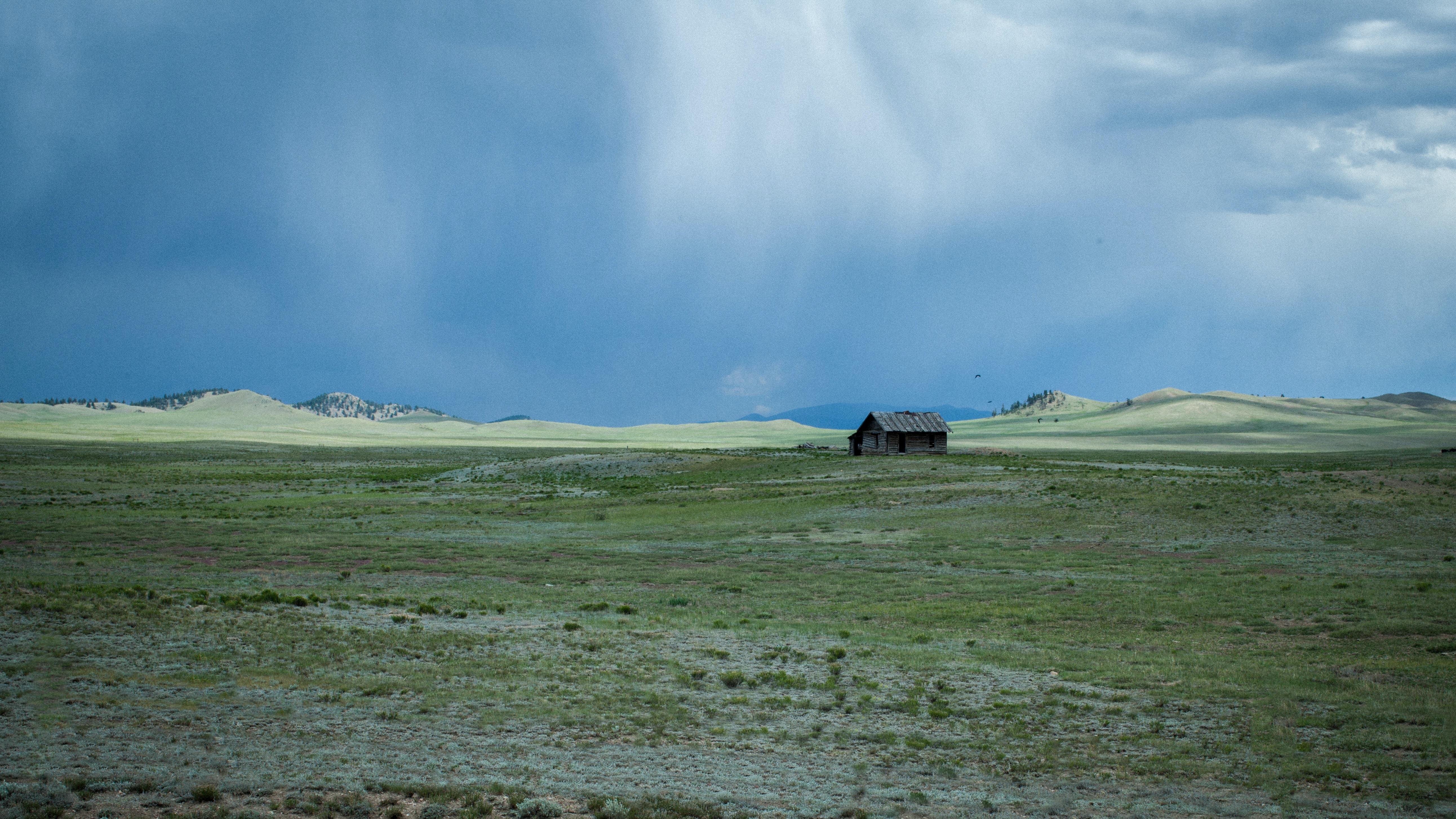 A bleak landscape with a wooden cabin on a desolate plain