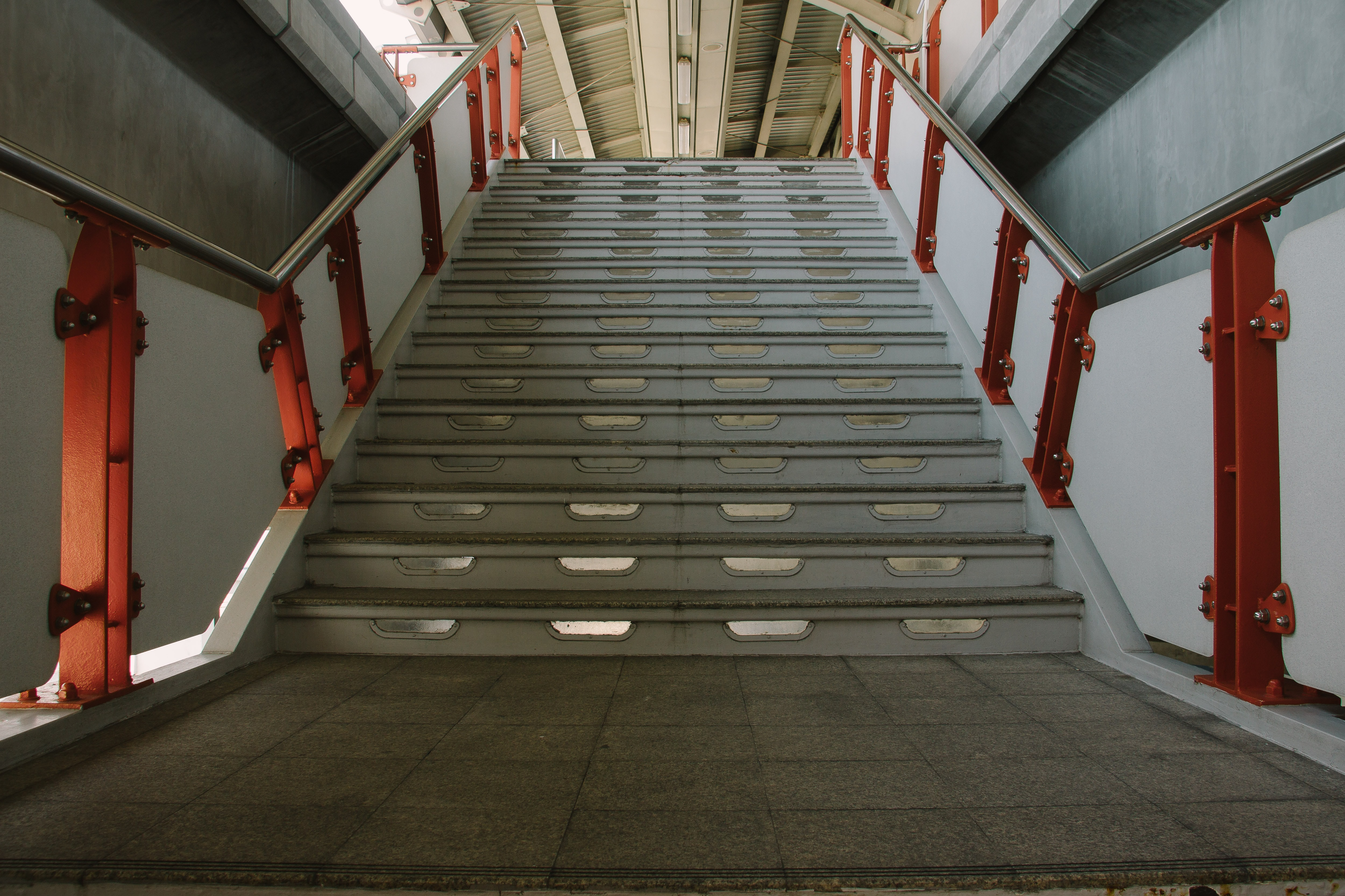 A train station staircase with red steel banisters