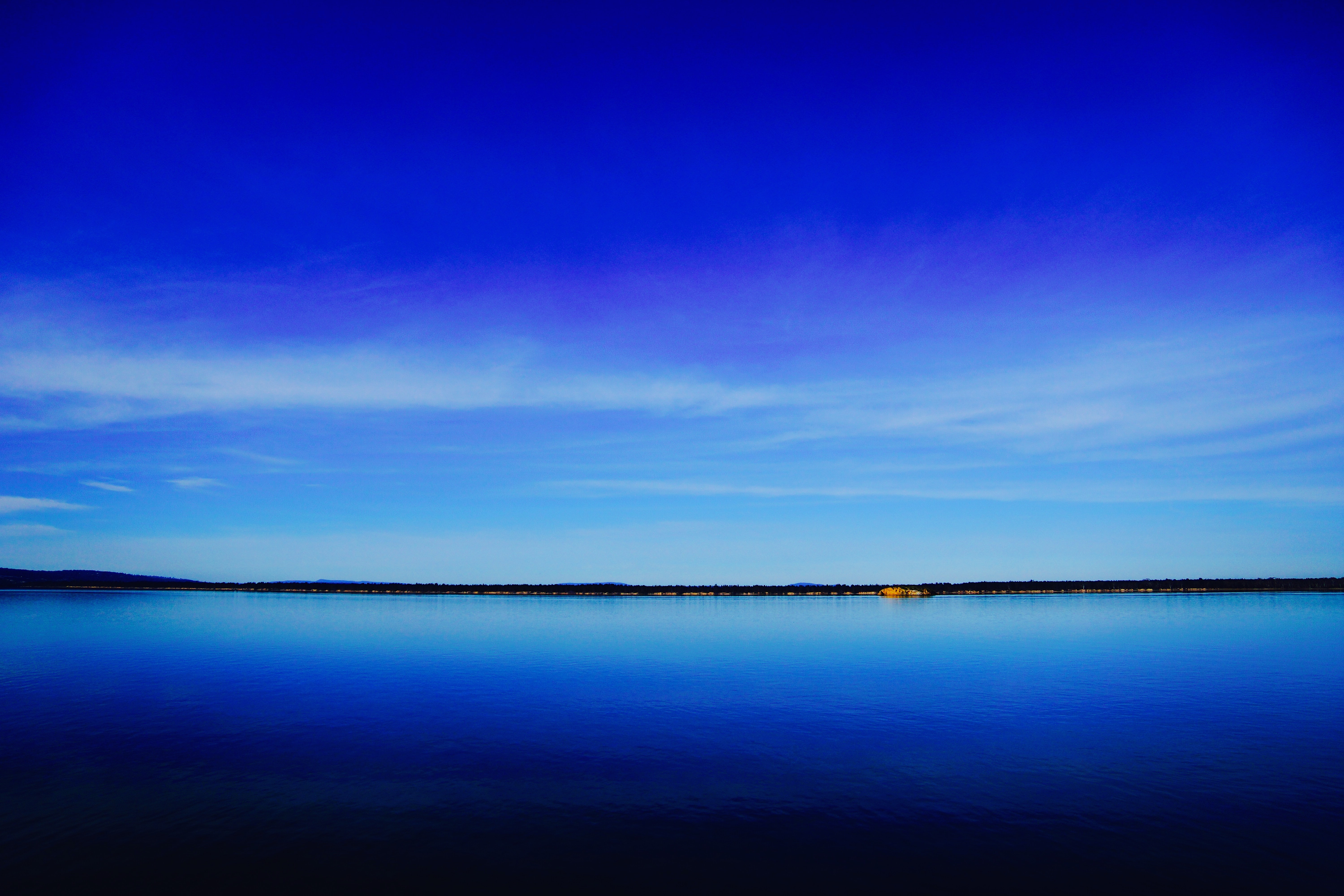 A deep blue lake and clear sky separated by a dark green shoreline on the horizon