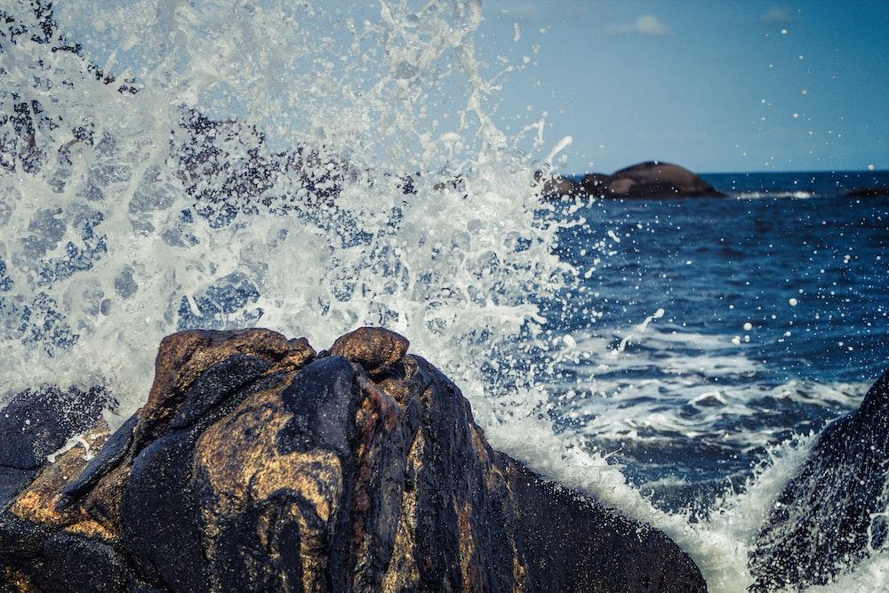 seawater splashing rock boulders at daytime