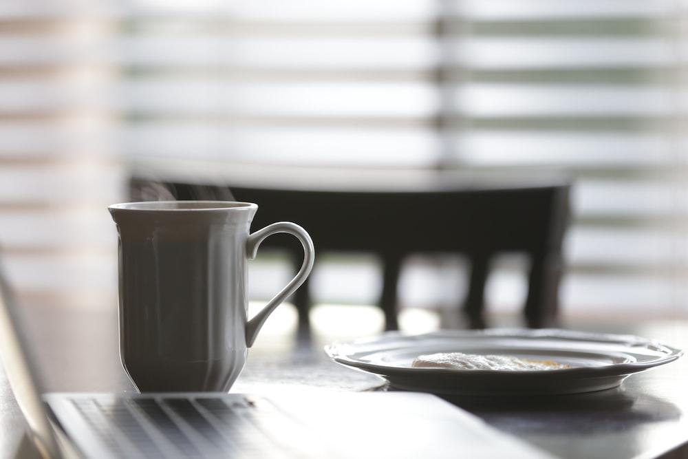 white ceramic mug beside plate on table