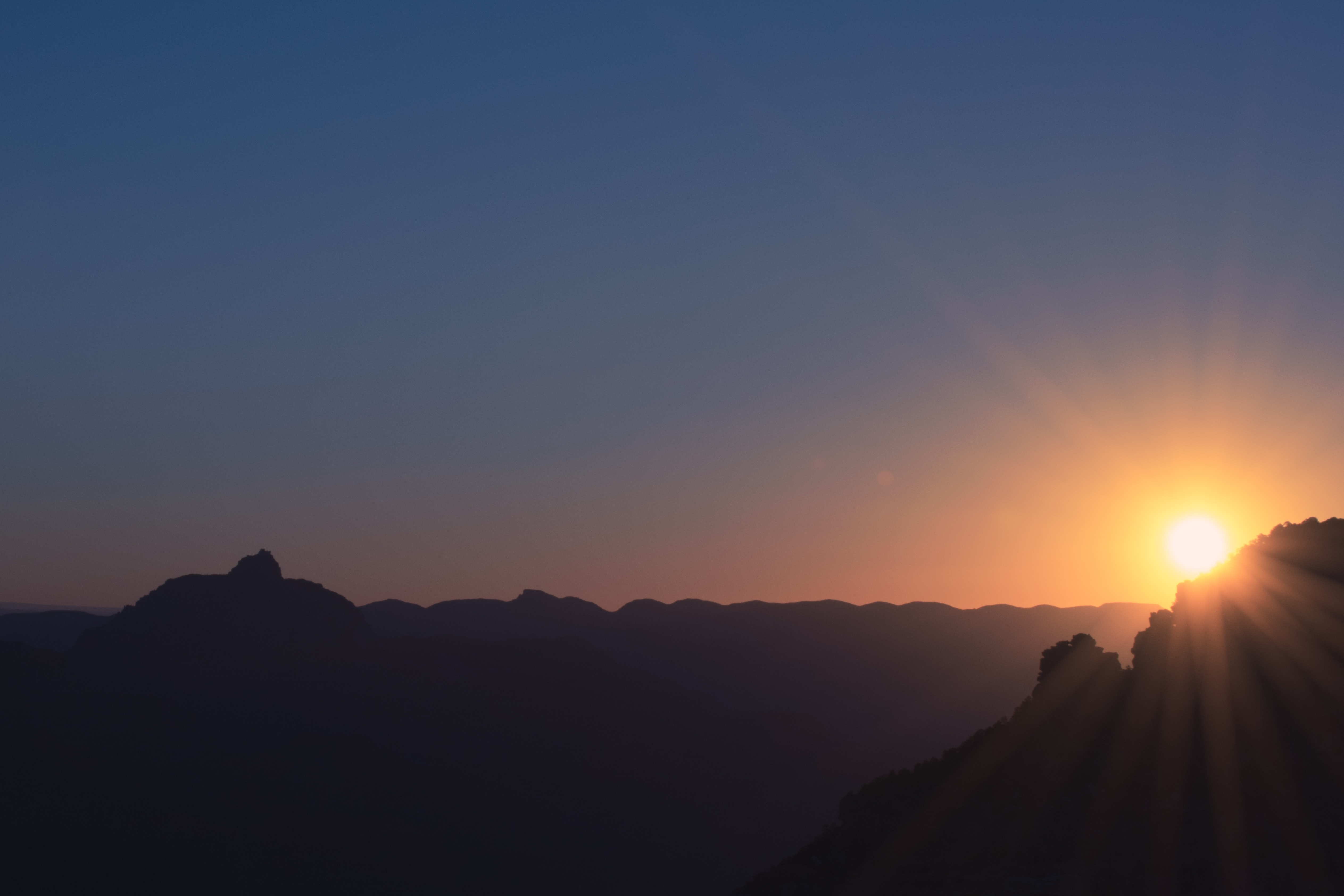 A sunset over a silhouette of an undulating mountain range