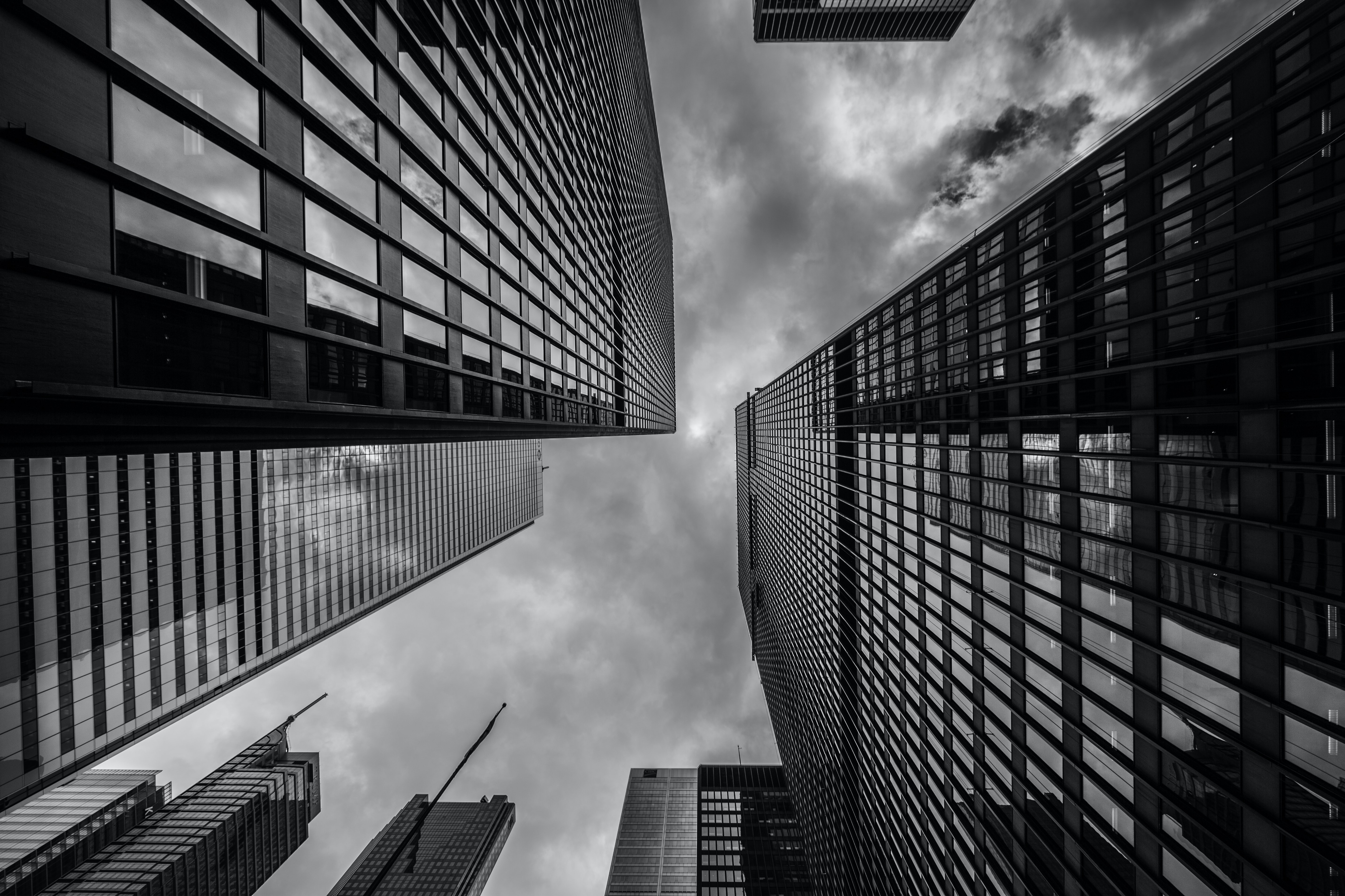 A black-and-white shot of white clouds above towering high-rises in a city